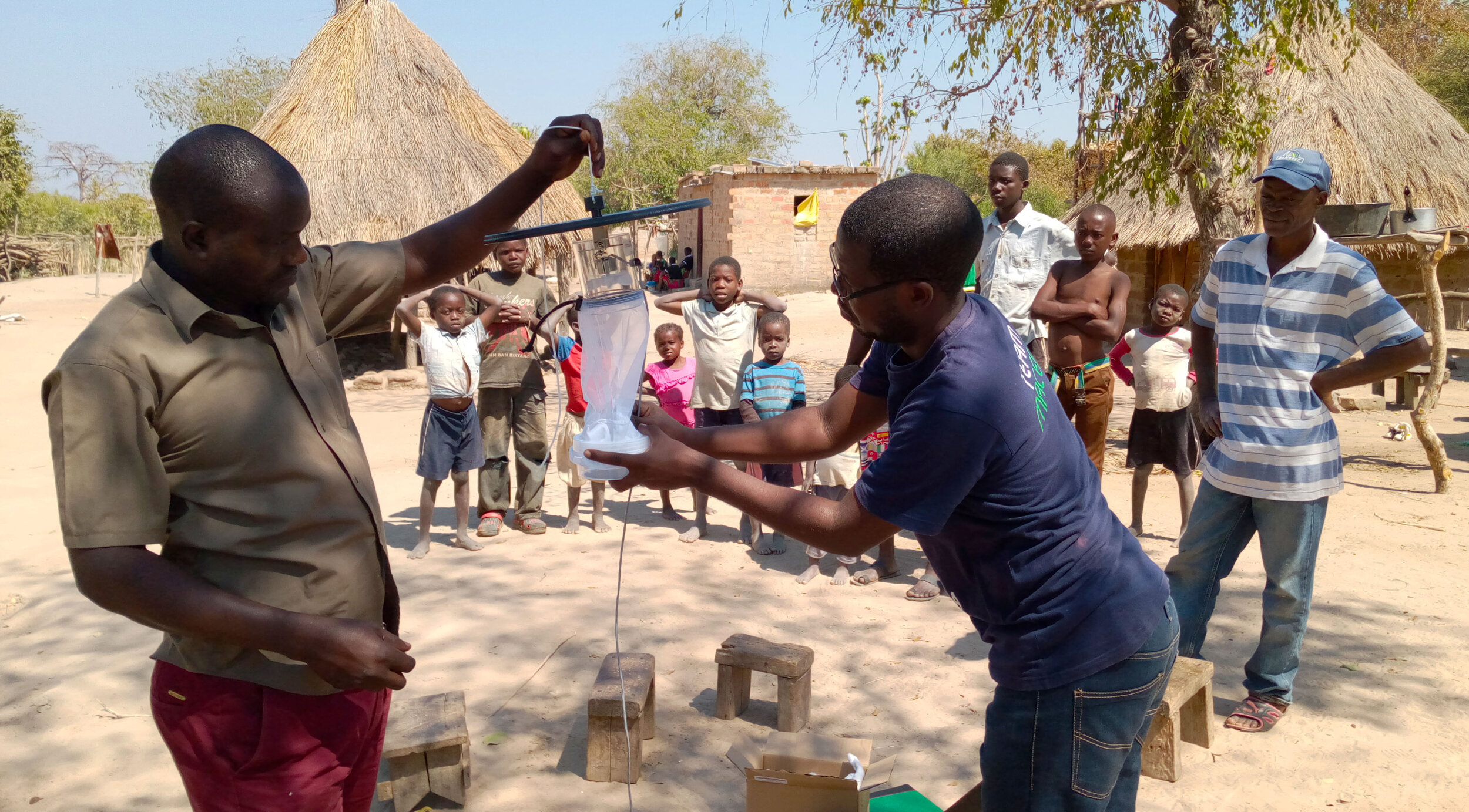 Entomological surveillance officer Javan Chanda demonstrates to a Community Health Worker how to assemble a CDC-Light Trap for collecting adult mosquitoes in Sinazongwe