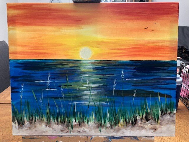 A photo of a painting of a sun setting by a waterfront.