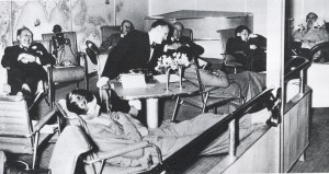 The passenger lounge (with grand piano for entertainment) where passengers could rest, eat, sleep and socialize during the flight.     (Below) A two-berth cabin on the Hindenburg. A wash basin was included in each small cabin, with the toilets and shower on another deck.
