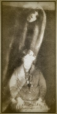 A fairly standard spirit photograph of the Spiritualist era, showing the allegedly dead daughter of the woman in the photograph.