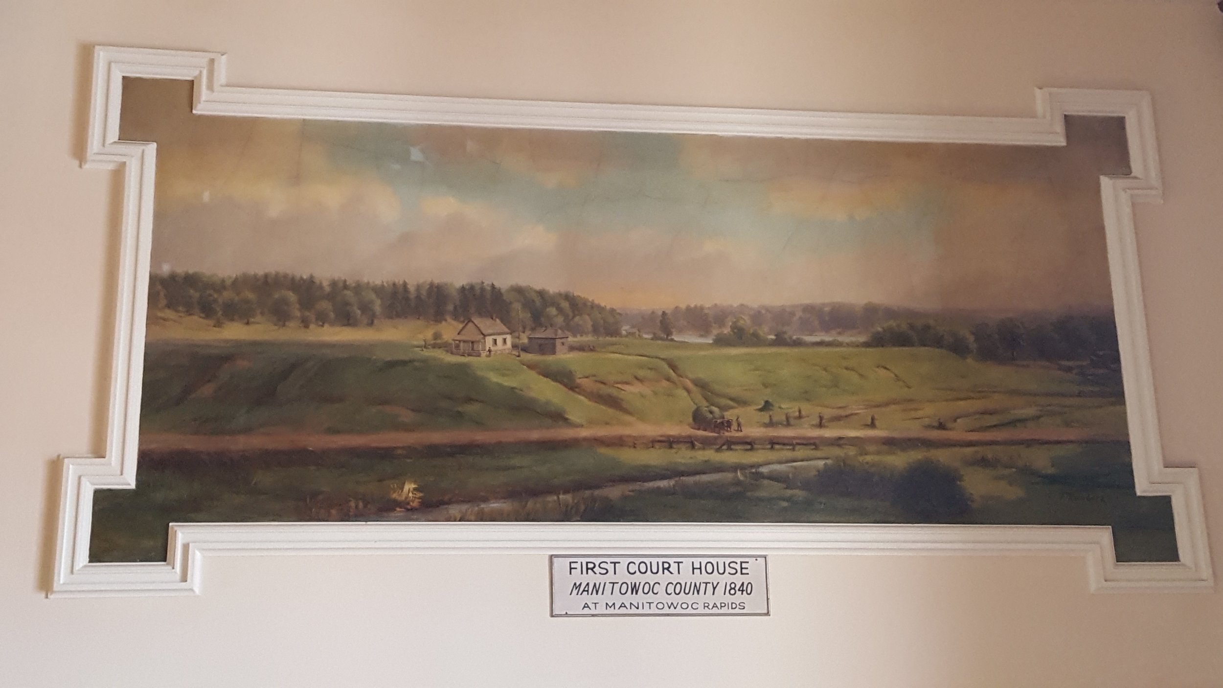 The First Court House and Jail at Manitowoc Rapids mural,painted by Franz Rohrbeck in 1912, is located in the west staircase at the Manitowoc County Court House.