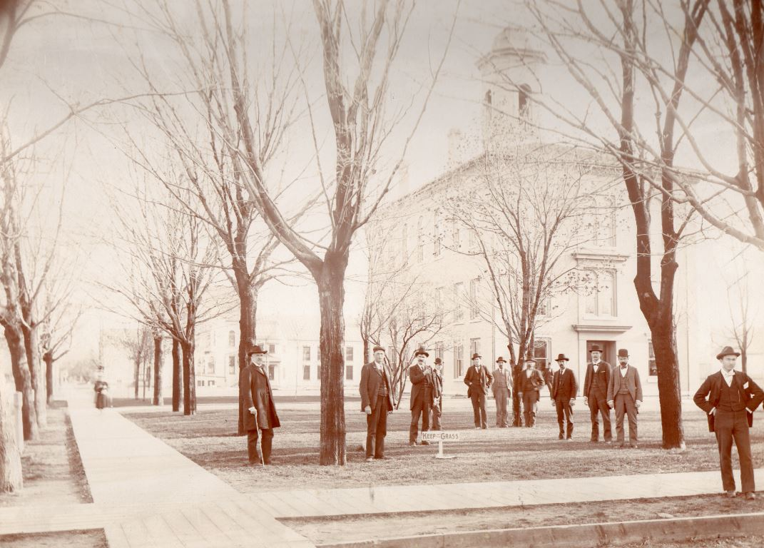 Officials of the County Courthouse with the courthouse in the background, Manitowoc, circa 1897