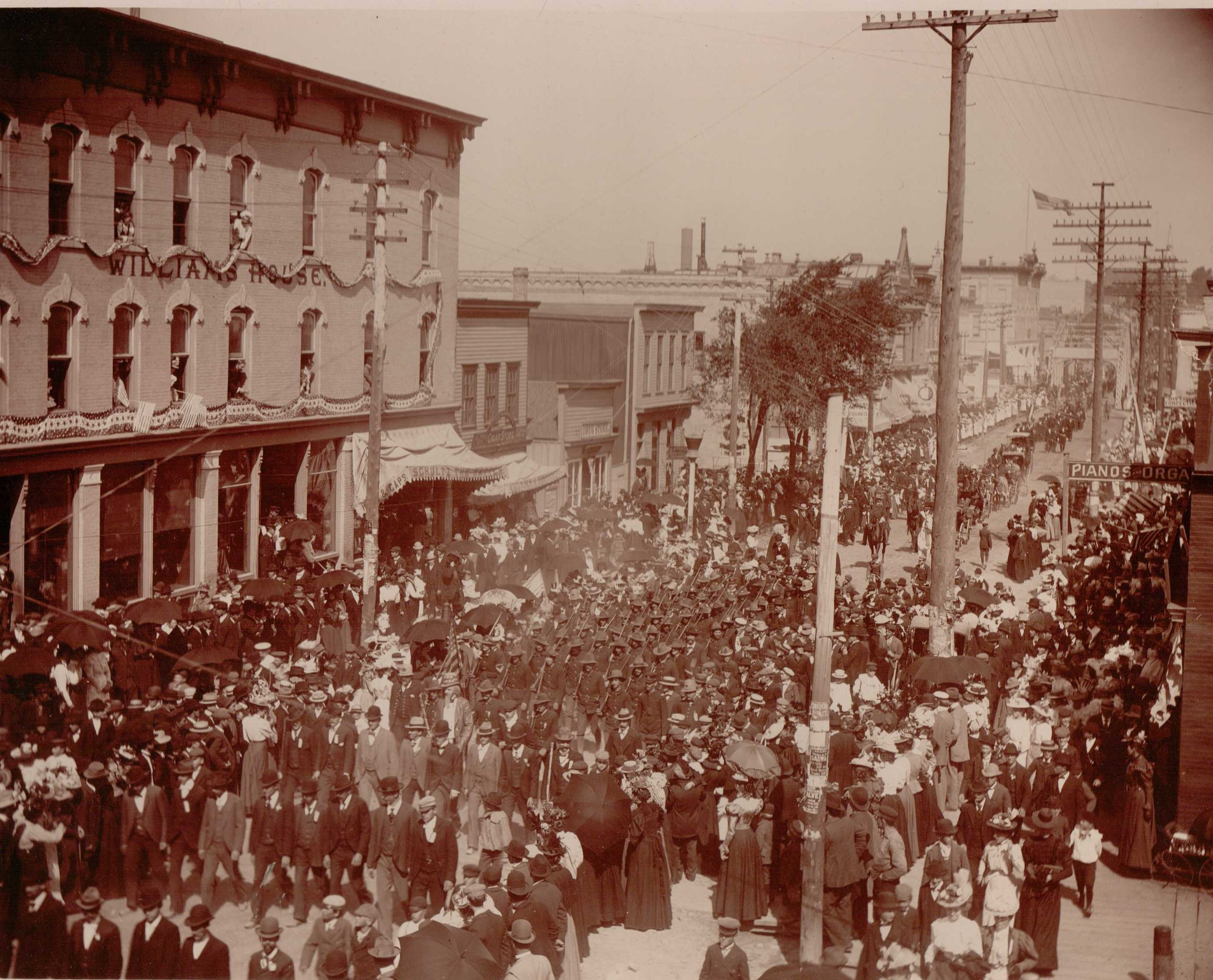Crowd and parade of Company H on South 8th Street in Manitowoc, in front of Williams House, after Spanish American War.