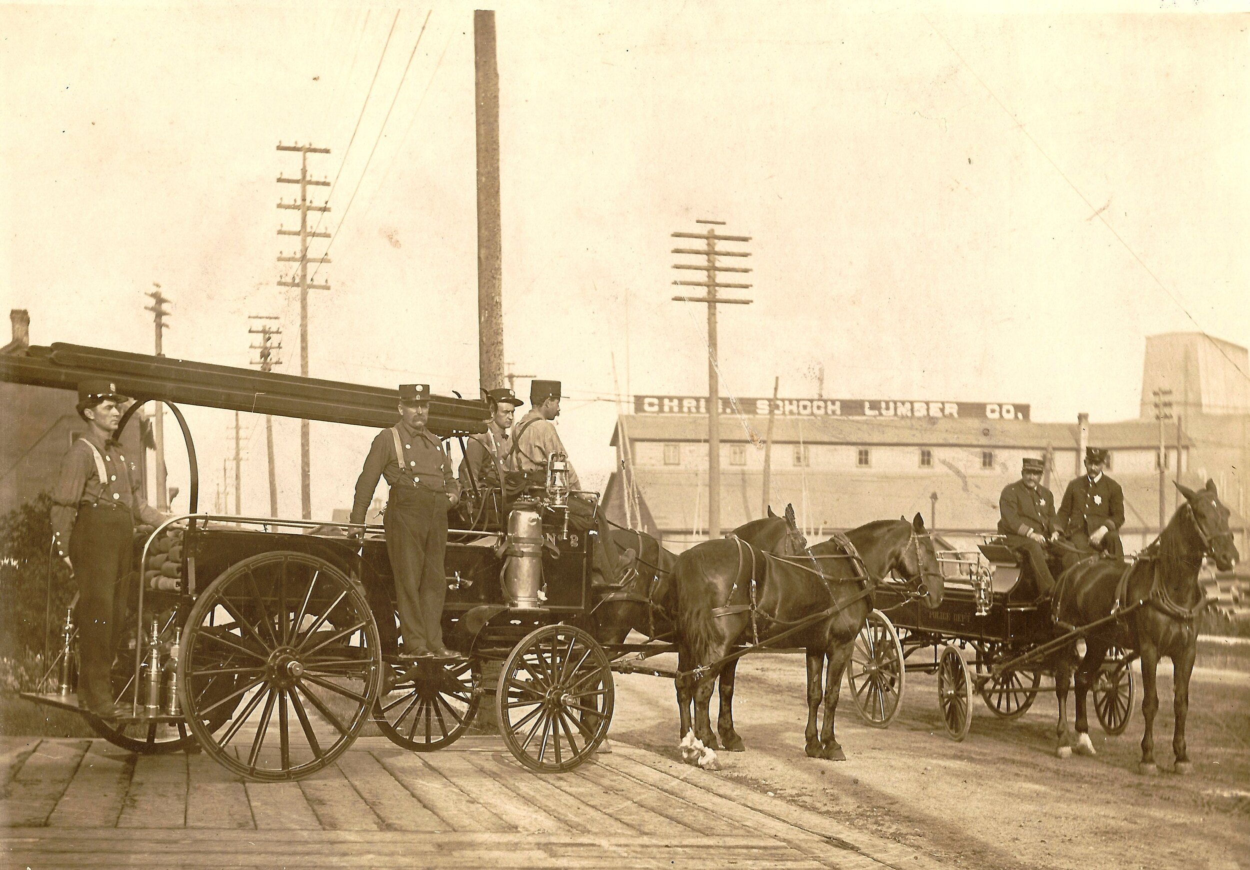 Horse drawn fire wagon with 4 firemen and single horse wagon with 2 men in front of south side firehouse at 911 Franklin St., Manitowoc. View to northwest is the Chris Schoch Lumber Co., seen in the back. Early 1900s.