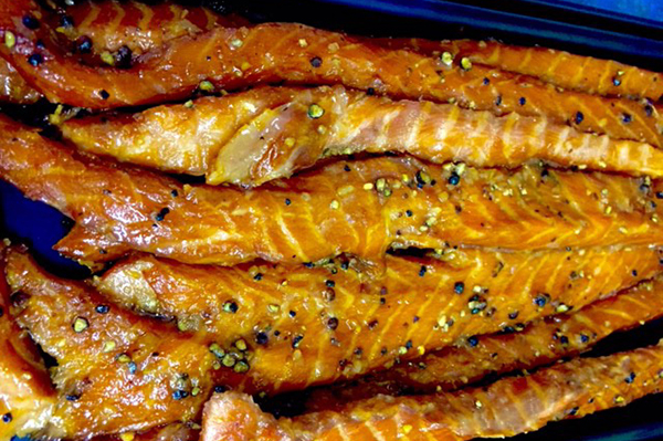 CANDIED GARLIC PEPPERED STRIPS Full strips of fresh salmon bellys sweeten similar to the candied salmon, but with a bite of heat from the garlic and peppercorn.