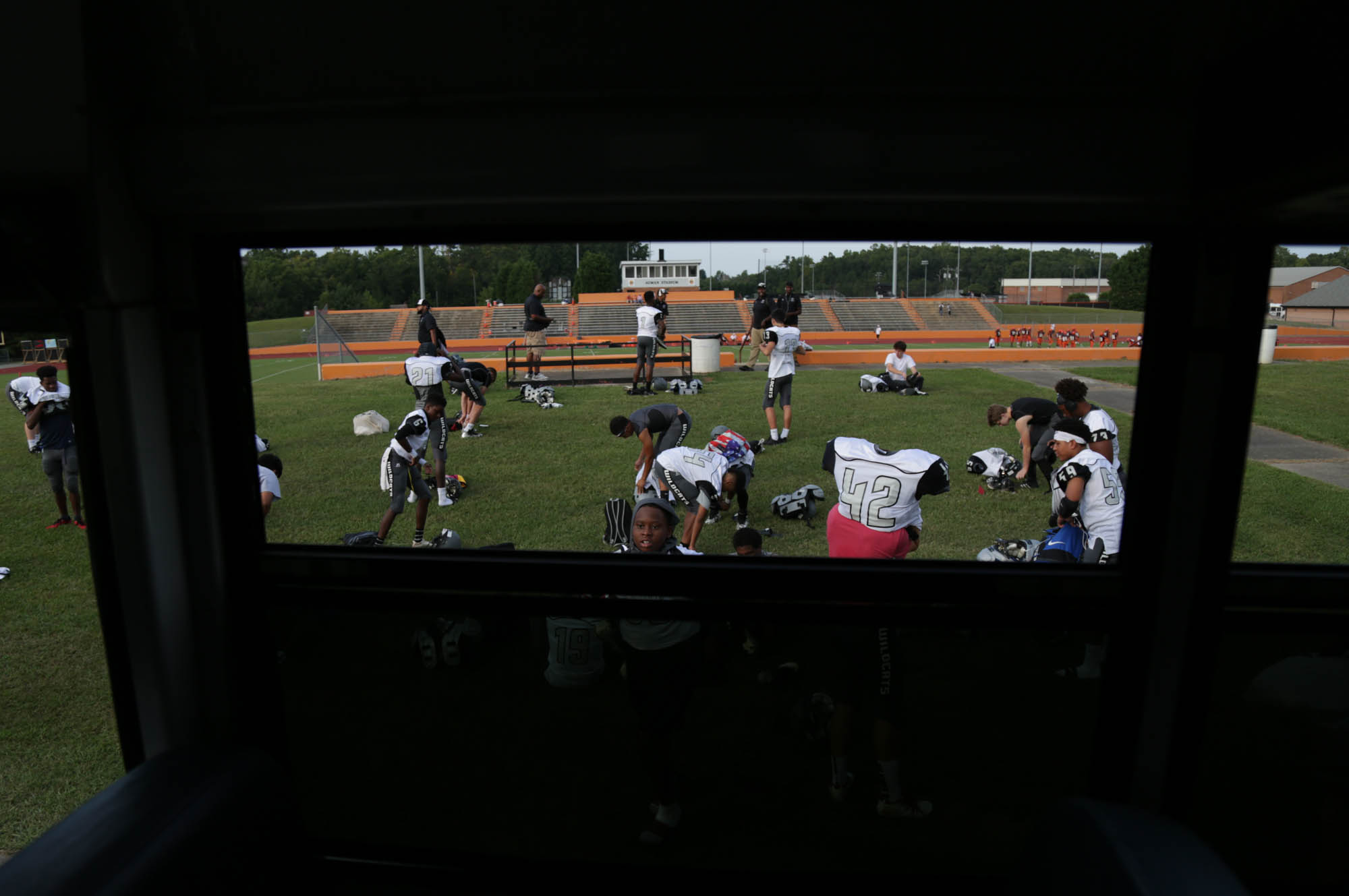 "Players get ready outside of Orange High School's football stadium. As a JV team, they don't usually get into locker rooms, creating a bonding experience when they all put on their gear together outside. ""We built a brotherhood this year and that's really important. We played for each other,"" said Jeffrey Monroe, a junior halfback."