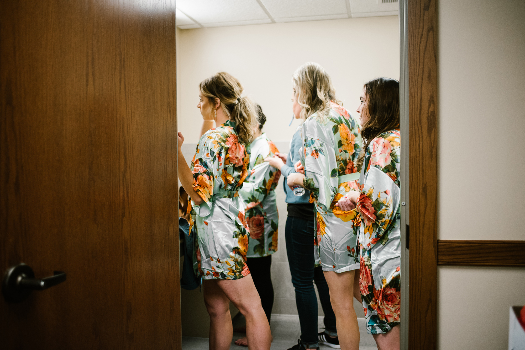 Bridesmaids getting ready in church bathroom