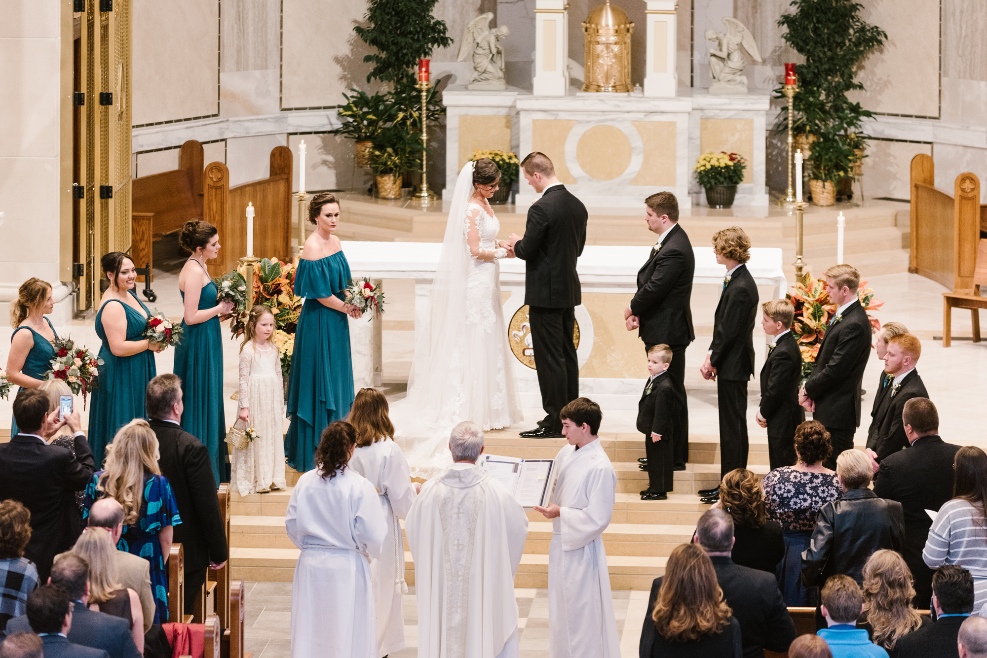 bride and groom exchanging rings at catholic church