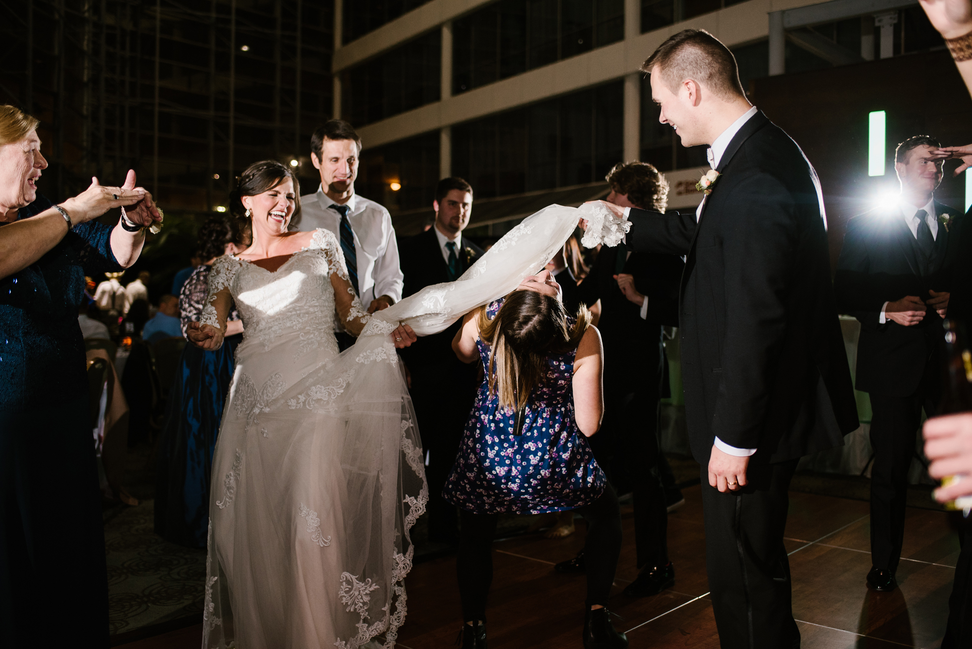 guest doing the limbo under bride's dress at wedding reception