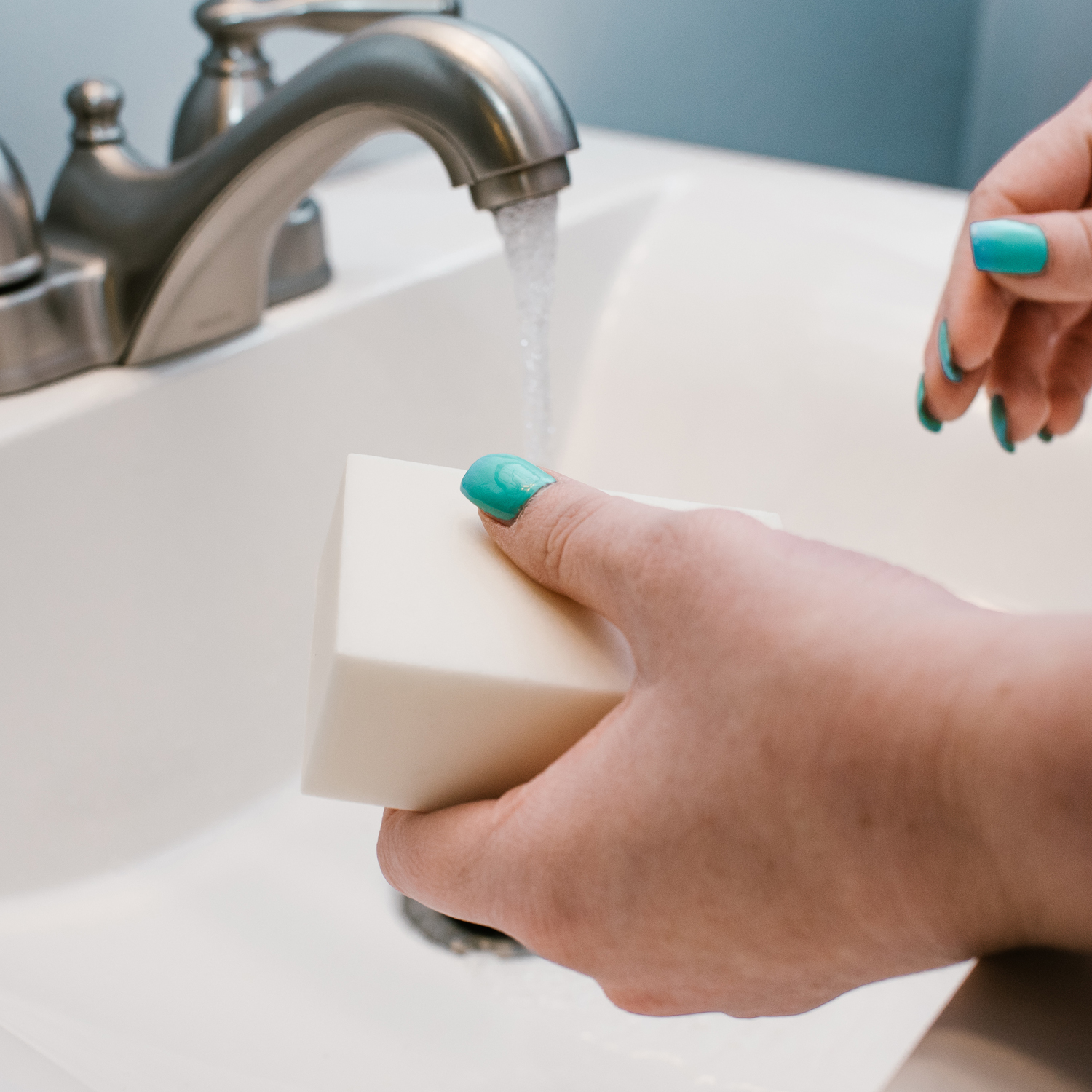 woman washing hands with bar of soap