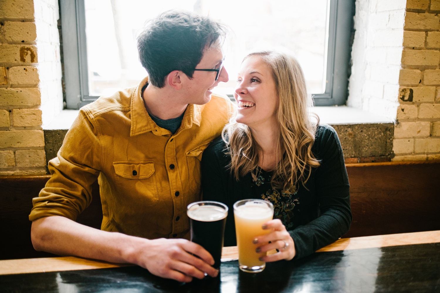 couple looking at each other smiling with beer at oddsides ales in grand haven michigan