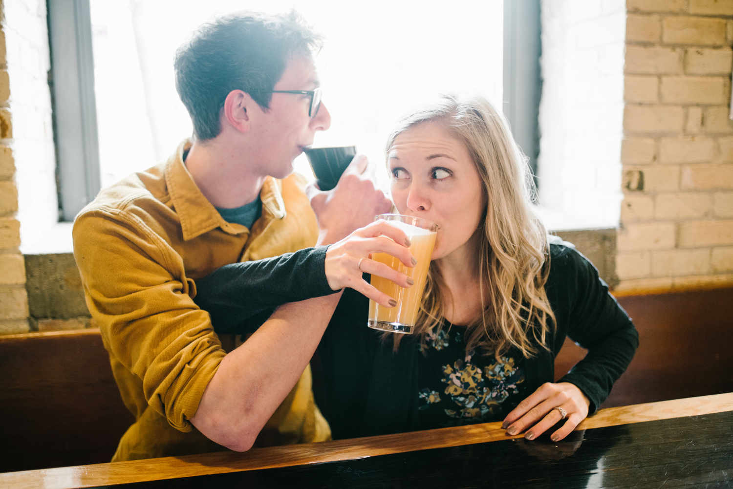 couple drinking craft beer at engagement session in grand haven michigan