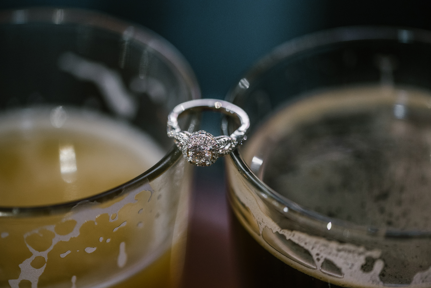 engagement ring balanced on two glasses of beer