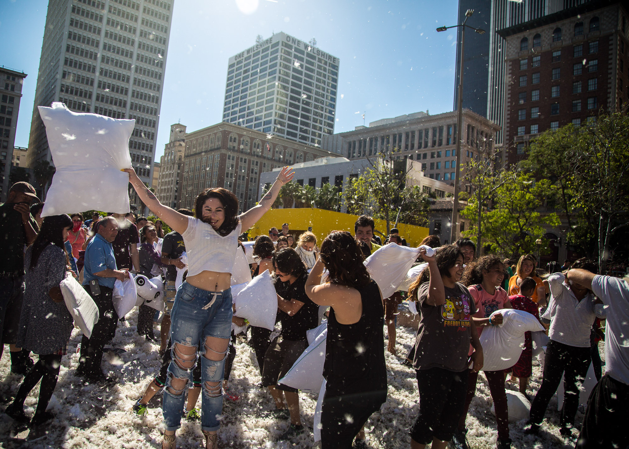 Participants take part in a giant pillow fight as feathers fly in Pershing Square in Downtown Los Angles on Saturday, April 1 2017. Hundreds of people traded soft blows in a giant pillow fight that dwarfed even the biggest slumber party slugfest. The annual event is held to celebrate International Pillow Fight Day as children, teens, adults and seniors swung pillows at one another for over 2 hours during Saturdays event. (Corsair Photo: Matthew Martin)