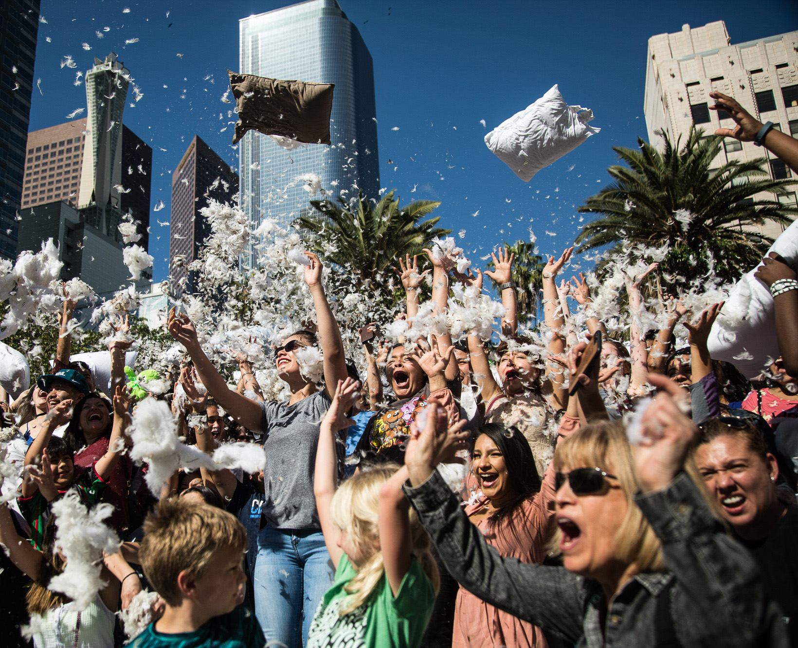 Participants of the International Pillow Fight Day cheer and scream while throwing pillows and feathers in the air in Pershing Square in Downtown Los Angles on Saturday, April 1 2017. Hundreds of people traded soft blows in a giant pillow fight that dwarfed even the biggest slumber party slugfest. Children, teens, adults and seniors swung pillows at one another for over 2 hours during Saturdays event. (Corsair Photo: Matthew Martin)