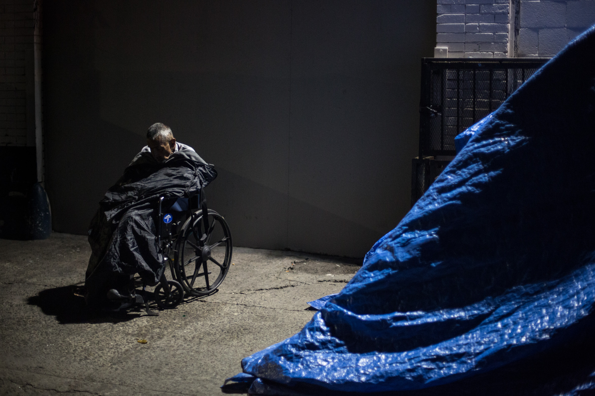Beneath a street light on Skid Row, an elderly man dozes off under a sleeping bag in Los Angeles, California. Next to him is a large tent made of blue tarp and found material. Apr. 2, 2017 (Staff Photographer Zin Chiang)