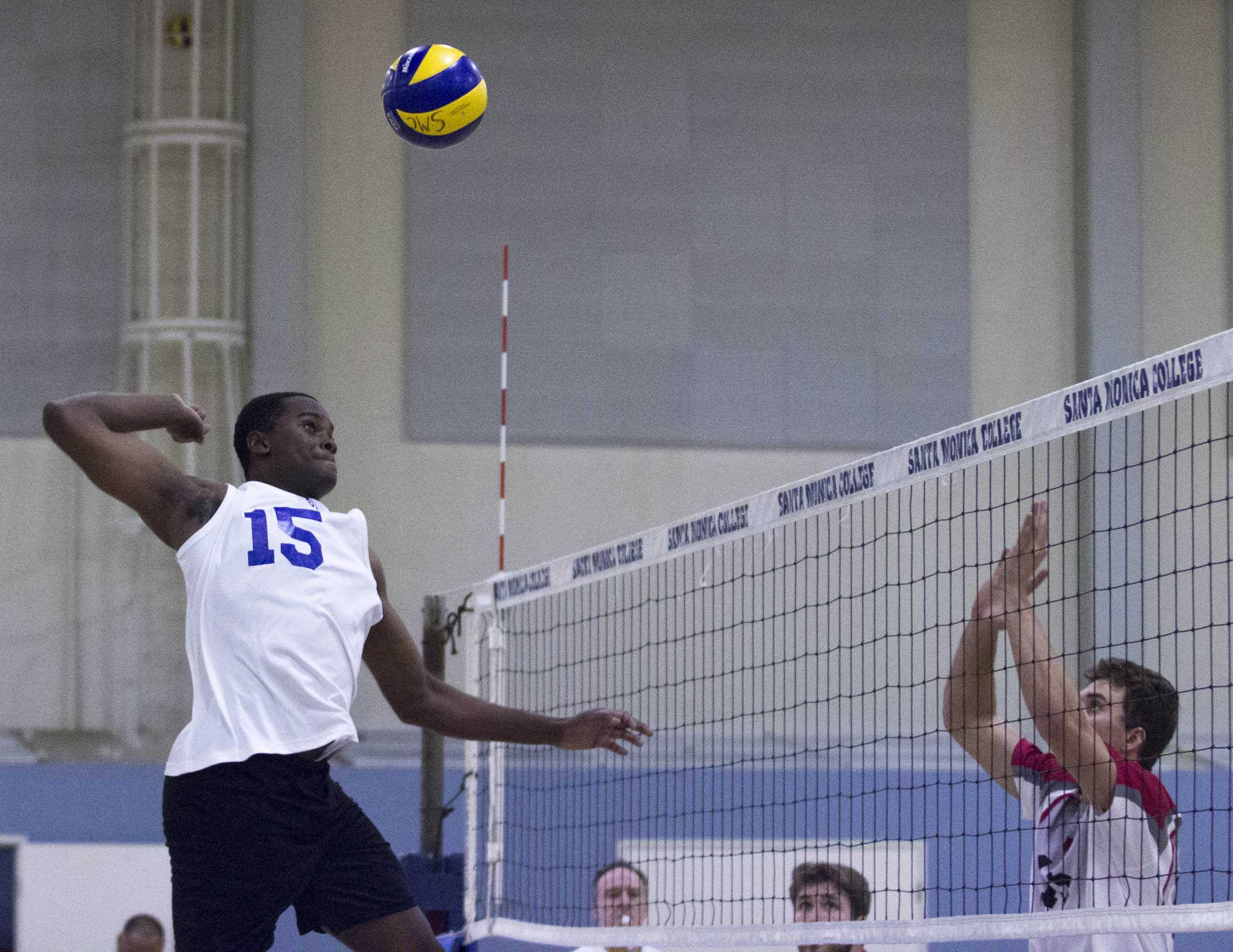 Santa Monica College Corsair freshman middle hitter Vecas Lewin (15, left) prepares for a spike as The Pierce College Brahmas outside blocker attempts to block the shot in the SMC Gymnasium at Santa Monica College in Santa Monica, CA. on wednesday, March 1, 2017. On the way to the Corsairs clean sweep of the Brahmas (3-0). (Corsair Photo: Zane Meyer-Thornton)