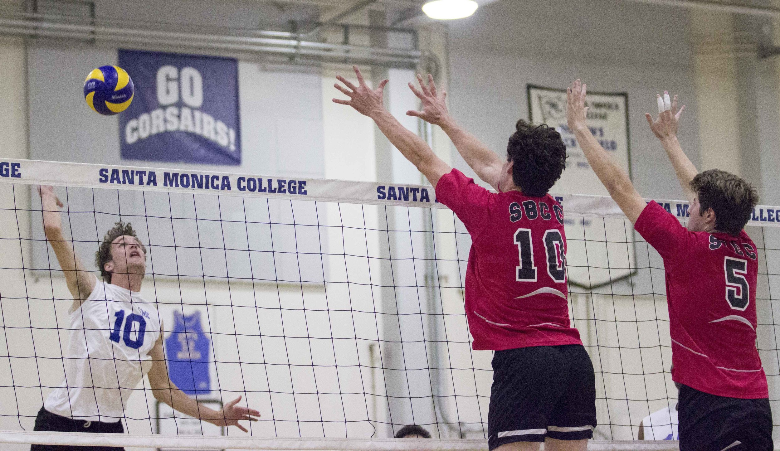Santa Monica College Corsairs sophomore right side hitter Shane Stoklos (10, left) lines up a spike as Santa Barbara City College Vaqueros sophomore outside hitter Jackson Mcdonough (10, center) and sophomore middle blocker Jarrod Jordan (5, right) position themselves to block the shot during the Corsairs 3-0 victory in the Santa Monica College Gymnasium at Santa Monica College in Santa Monica California on March 15, 2017 (Photo By: Zane Meyer)