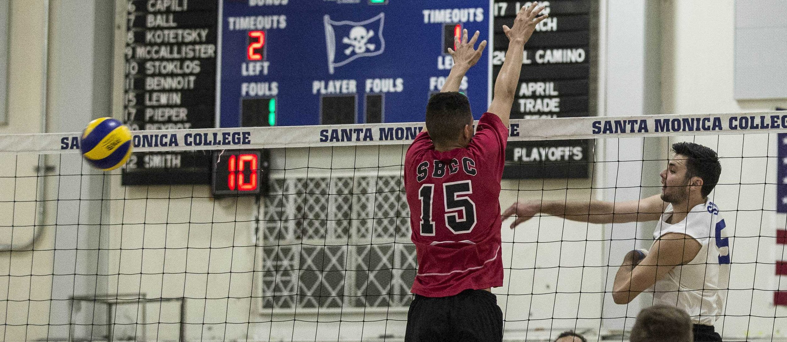 Santa Monica College Corsair freshmen right-side hitter Andrew Dalmada (5, right) successfully attempts a powerful spike as Santa Barbara Vaqueros freshman middle blocker (15, left) fails to defensively block the ball, allowing the Corsairs to score a point during the second set of the game in the Santa Monica College Gymnasium at Santa Monica College in Santa Monica California on March 15, 2017. The Santa Monica Corsairs were able to sweep the Santa Barbara Vaqueros 3-0 by the end of the game. (Corsair Photo: Matthew Martin)