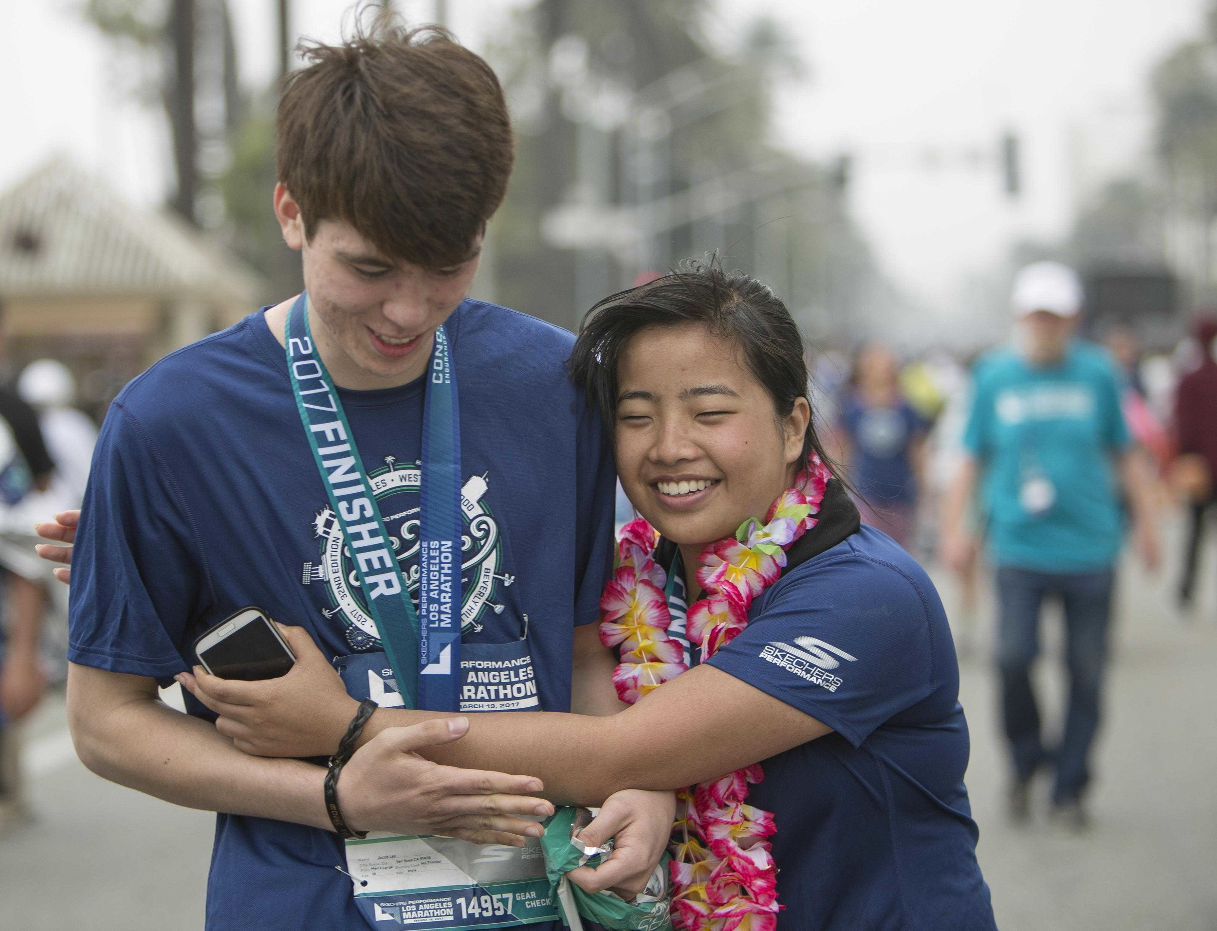 March 19, 2017. Kathy Pho (right) completes the 2017 LA Marathon and embraces her childhood friend Jacob Lee (left) who ran The LA Marathon along side her. Kathy Pho finished the marathon in five hours fourty nine minutes fifty four seconds. Santa Monica, California. Daniel Bowyer