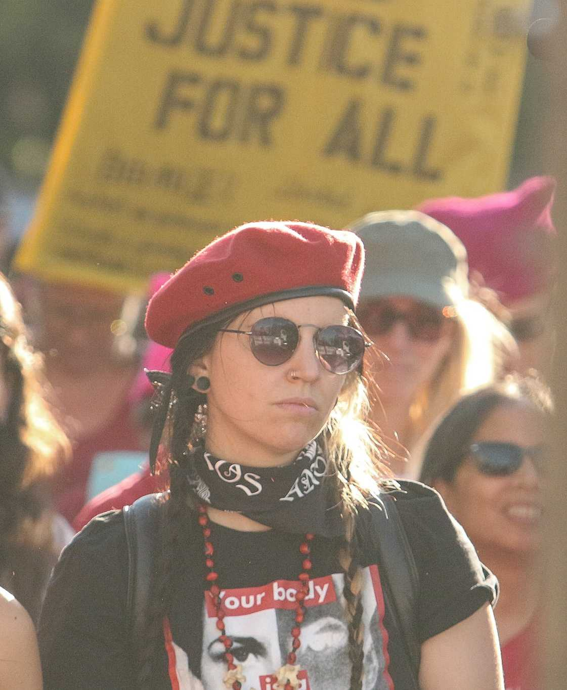 A member of the Women's strike listens to the speakers of the rally wearing red as a stand in solidarity in Downtown Los Angeles, California on March 8th (photo by José Aguila)