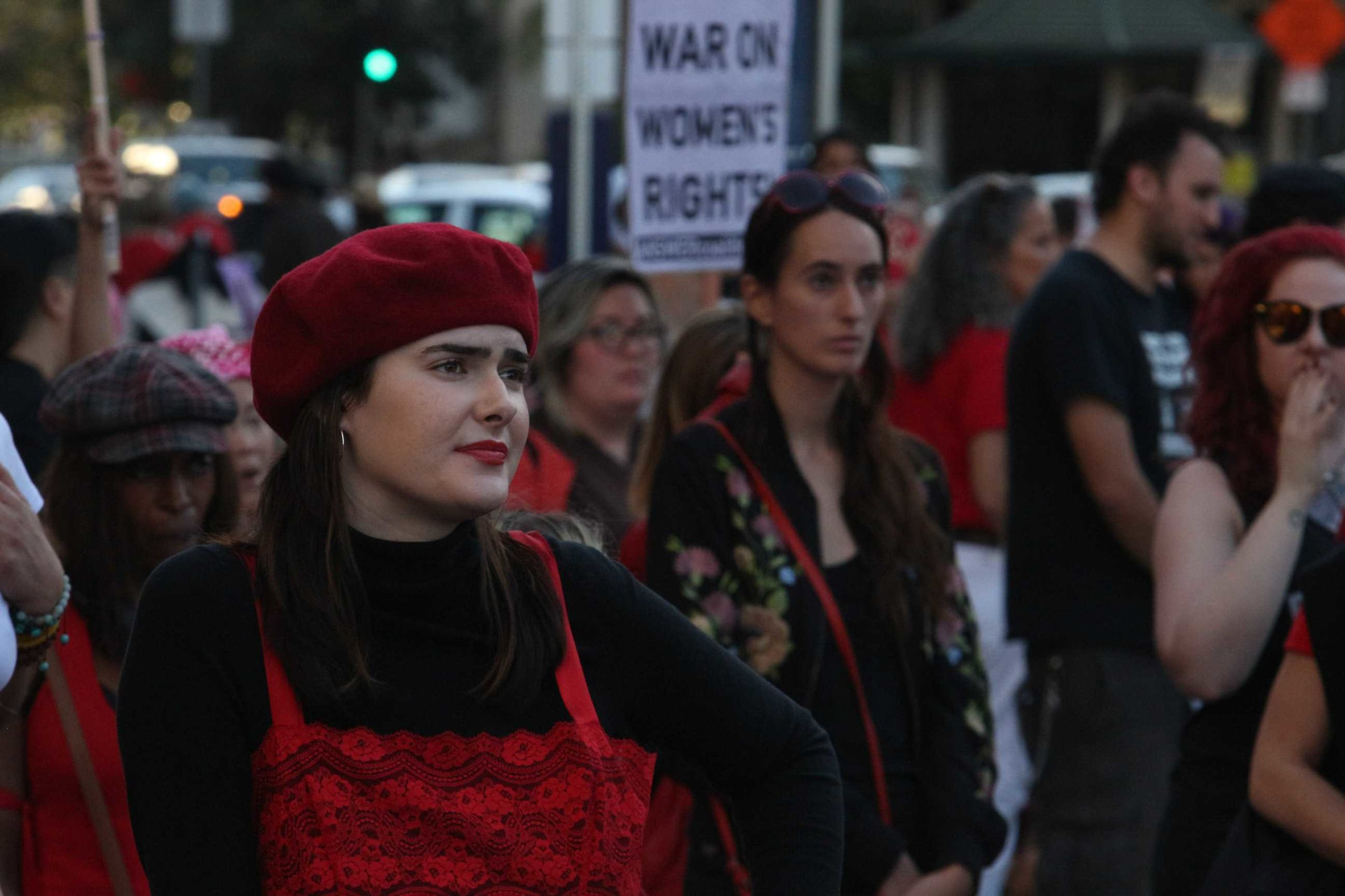 A member of the Women's strike listens to the speakers while wearing red as a stand in solidarity in Downtown Los Angeles, California on March 8th (photo by José Aguila)