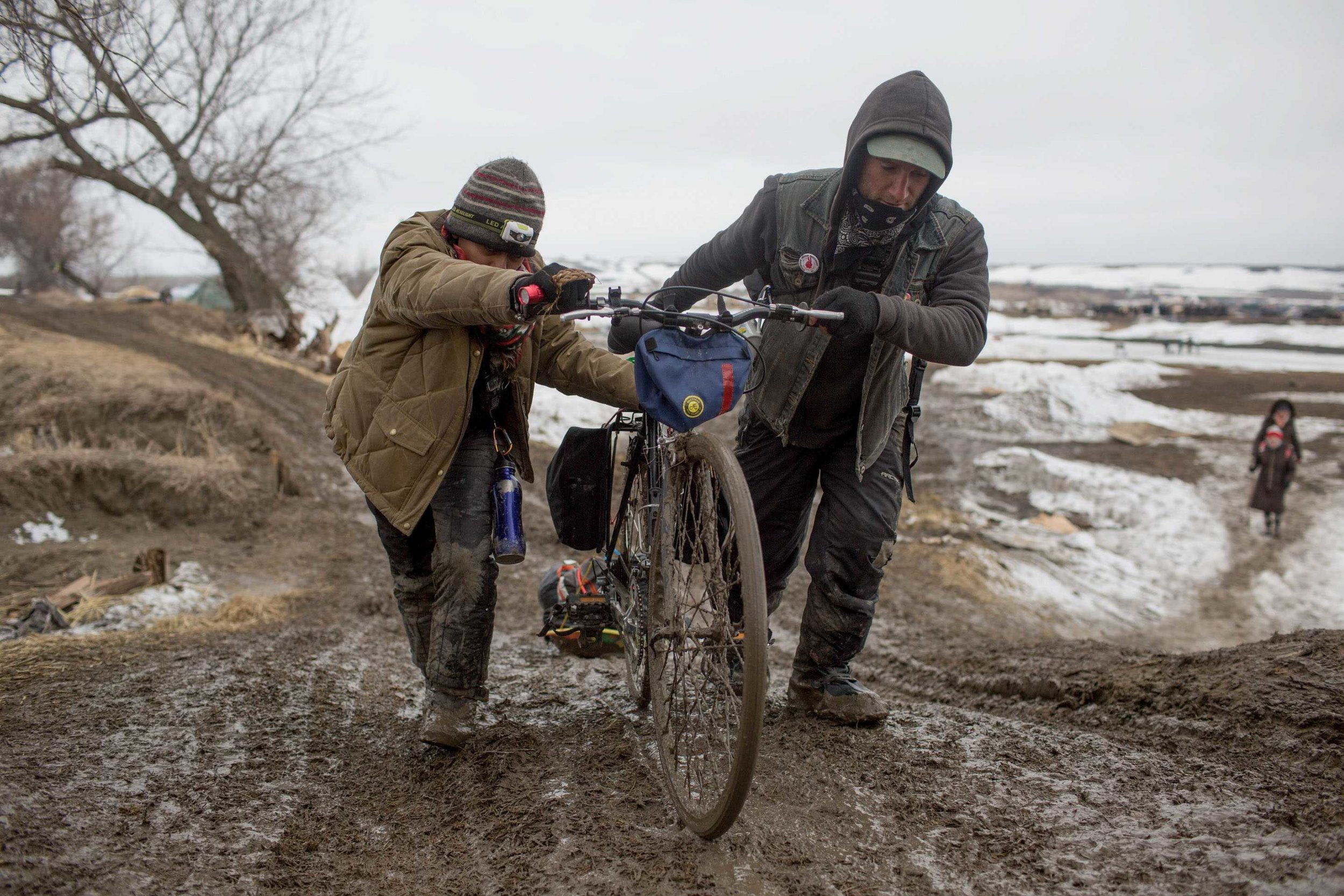 Water protectors push their bike up a hill in an effort to evacuate Rosebud Camp before Federal and state authorities (seen in the distance far right) move over the Cannonball River from Oceti Sakowin into the neighboring protest camps. Rosebud Camp, Cannonball, North Dakota Thursday February 23rd, 2017. by Ruth Iorio