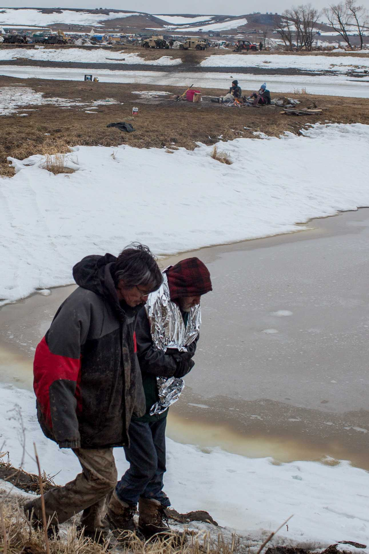 Elders retreat as in the distance hundreds of heavily militarized and armed police raid Oceti Sakowin camp, the protest camp established by the seven councils of the Lakota tribe in order to resist the proposed Dakota Access Pipeline. Photo by Ruth Lorio.