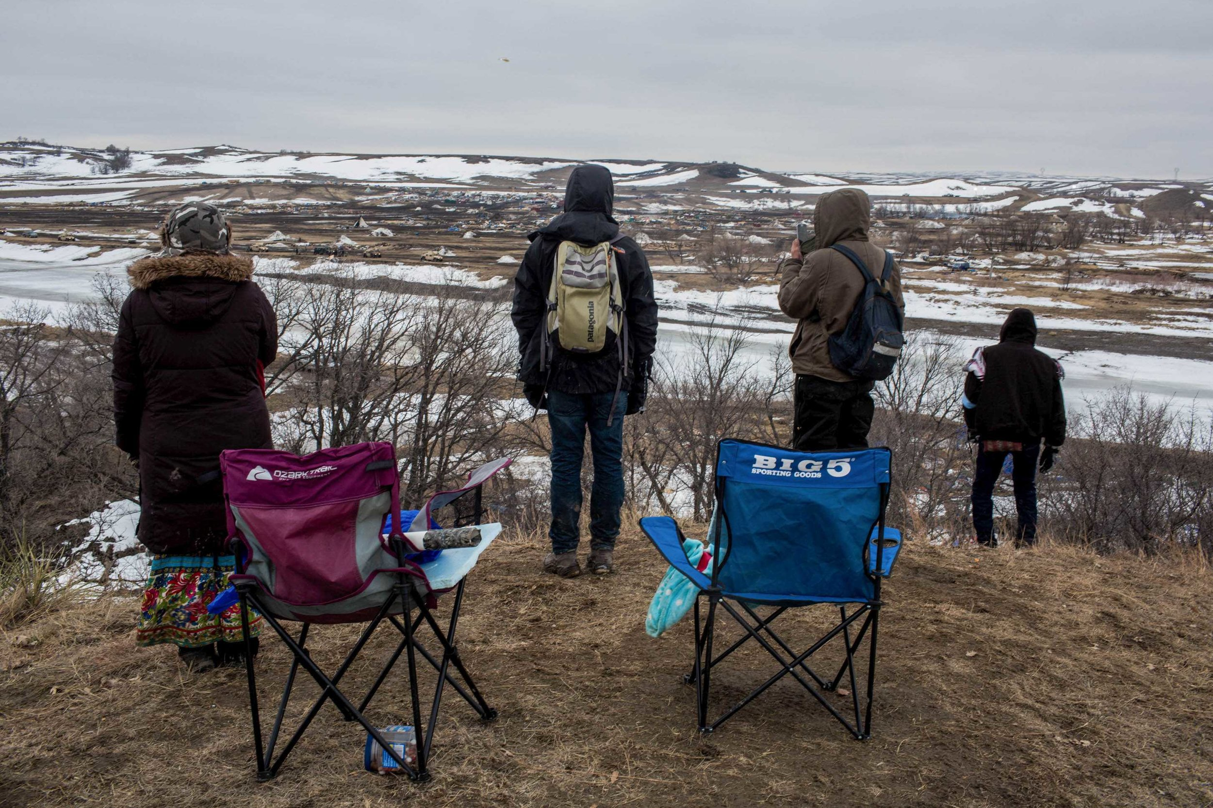 Water Protectors stand on the hill overlooking Oceti Sakowin, watching highly militarized BIA, ATF and Morton County Sheriffs bulldoze the remains of the camp several hours after the raid on Wednesday morning. Wednesday February 23rd 2017, Sacred Stone Camp, North Dakota. Photo by Ruth Lorio.