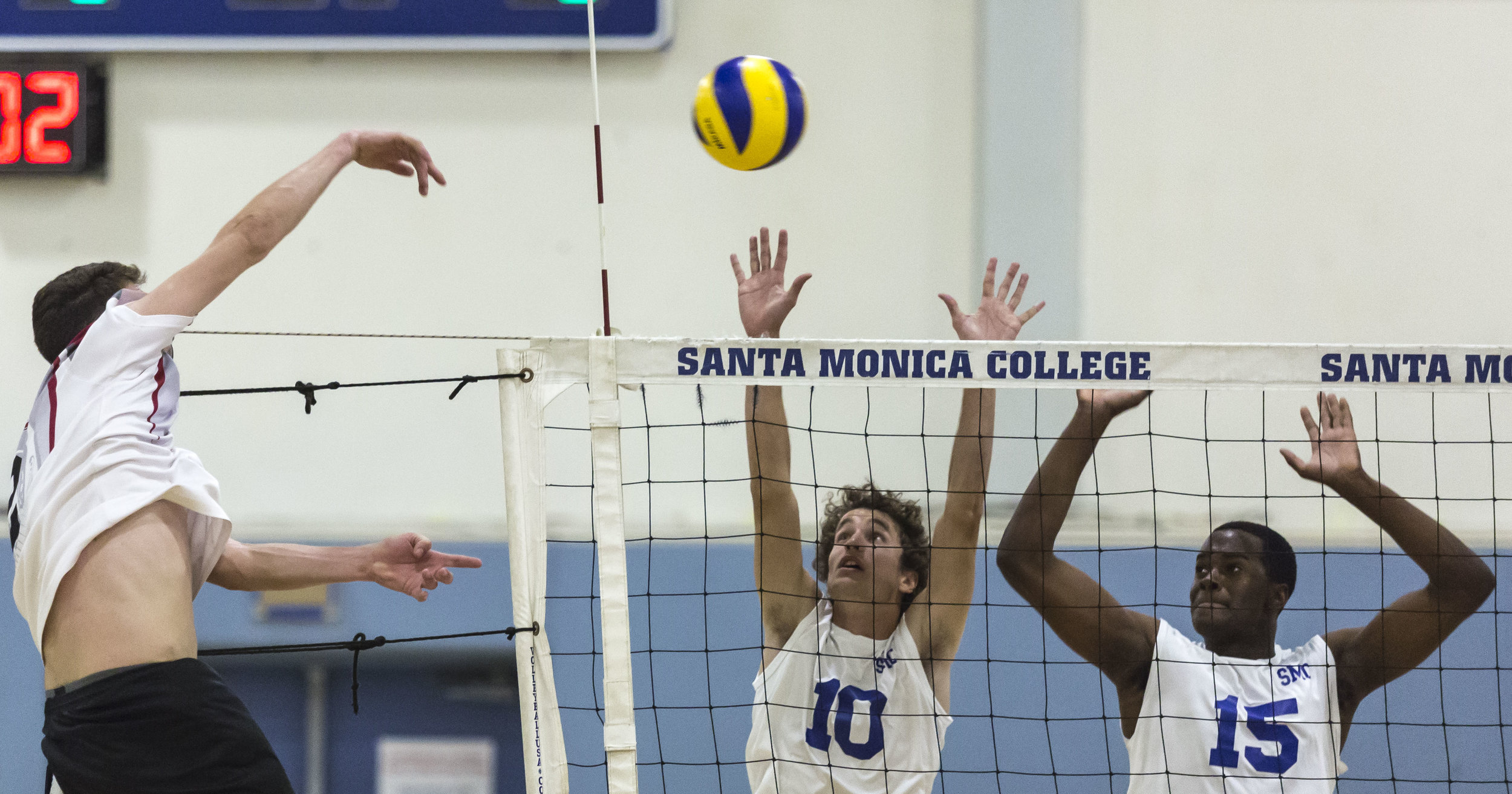 Pierce College Brahma freshmen opposite-hitter Trenton Sellers (2, left) powerfully spikes the ball into the Corsair defense as Santa Monica College Corsair freshmen right-side hitter Shane Stocklos (10, middle-right) and Santa Monica College Corsair freshman middle hitter Vecas Lewin (15, right) attempt to block it in the Santa Monica College gymnasium in Santa Monica Calif., on Friday, April 21 2017. The Corsairs however would go on to win the game 3-2, which would allow the Corsairs to advance to the second round of the CCCAA playoffs. (Corsair Photo: Matthew Martin)