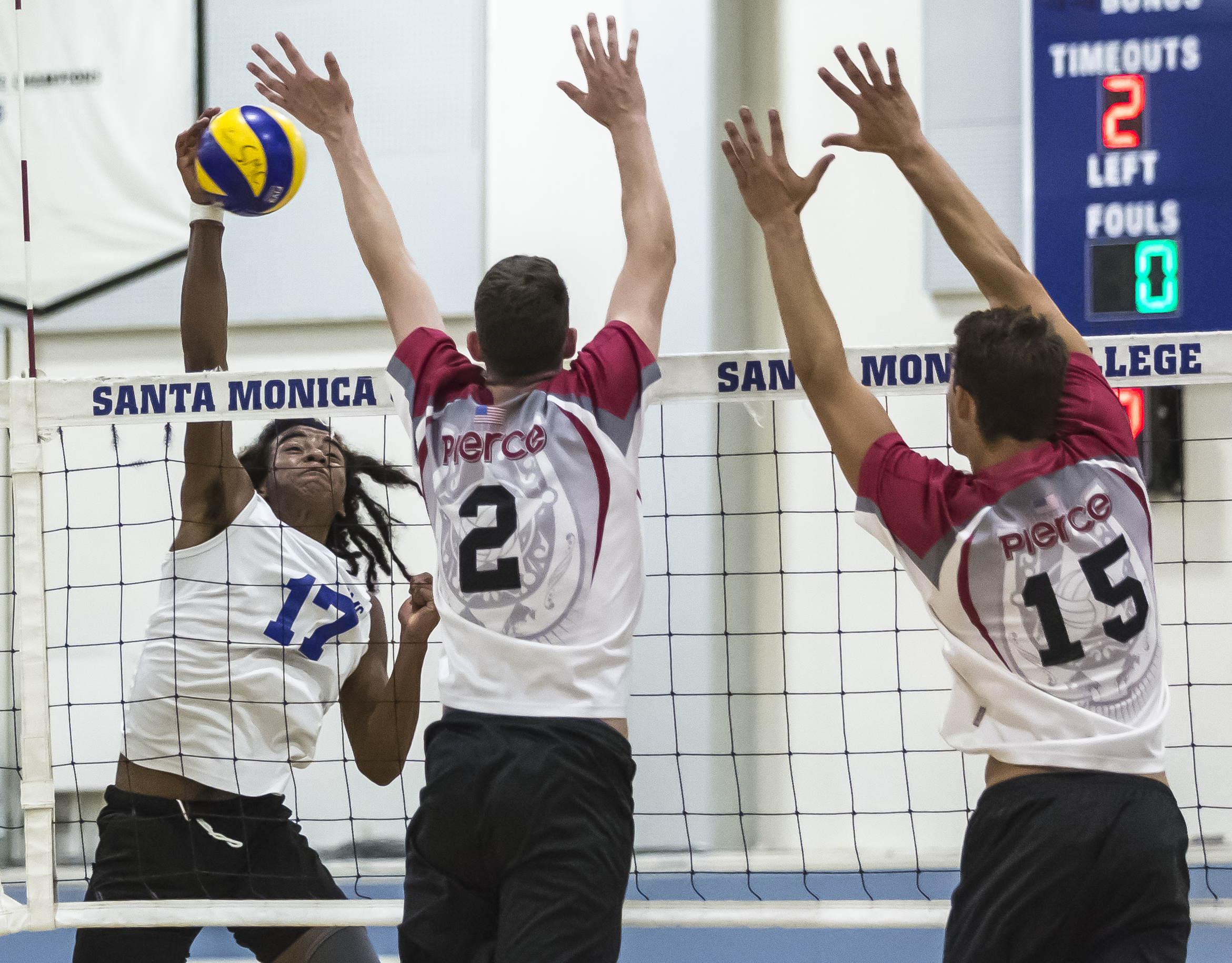 Santa Monica Corsair freshman outside hitter Dane Pieper (17, left) powerfully spikes the ball into the Pierce College defense as Pierce College Brahmas freshman opposite hitter Trenton Sellers (2, middle) and freshmen middle blocker Max Petuhov (15, right)prepare to block the incoming spike during the first set of the game in the Santa Monica College gymnasium in Santa Monica Calif., on Friday, April 21 2017. The Corsairs would go on to win the game 3-2, which would allow the Corsairs to advance to the second round of the CCCAA playoffs. (Corsair Photo: Matthew Martin)