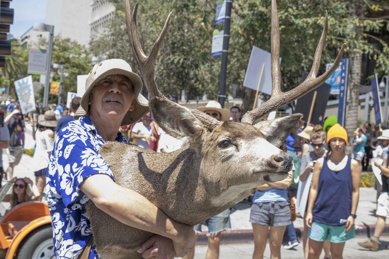 Mike Gloria, a protestor at the Earth Day March in Downtown Los Angeles, California on April 22, 2017 watches a choir presentation a he holds a deer head to show that when the earth goes, us and all the animals go with it. Zane Meyer-Thornton.