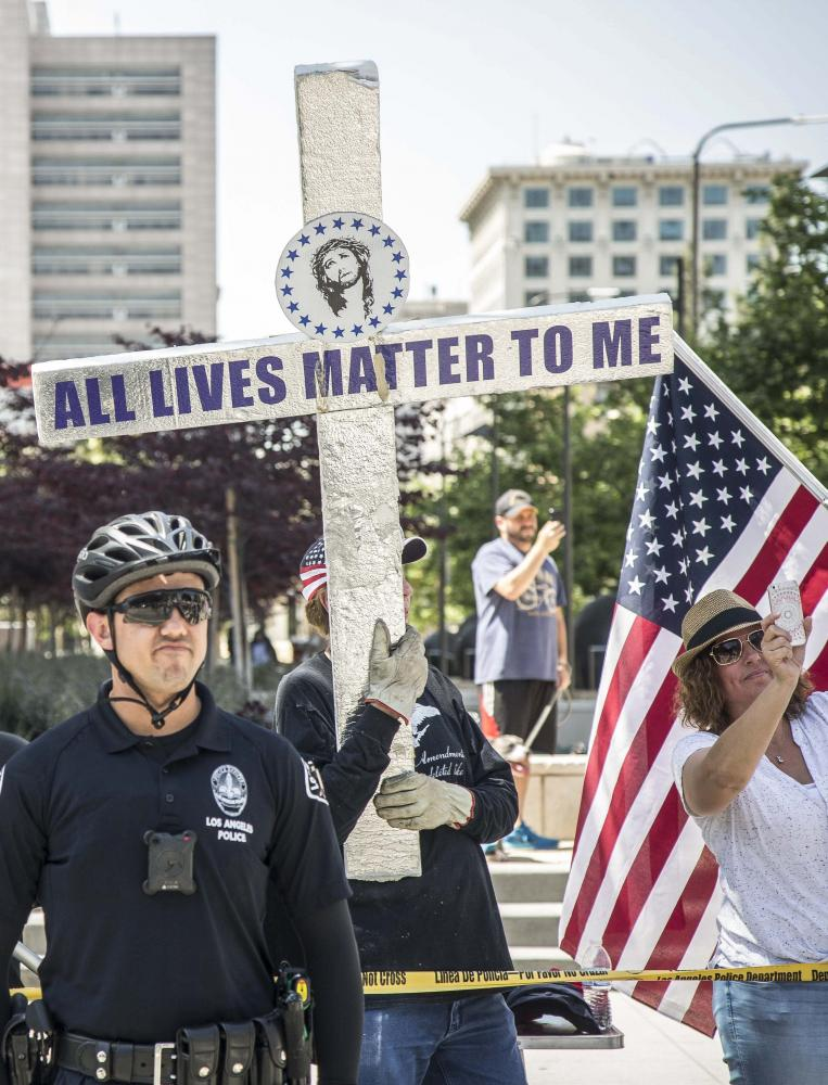 """Estimated two dozen Trump supporters gathered in front of the Los Angeles Police Department headquarters, across the street from City Hall, to voice their support for the president during the March for Science event in downtown Los Angles Calif., on Saturday, April 22 2017. The Trump supporters waved American Flags and pro Trump flags and held up a crucifix that had written on it, """"All lives matter to me."""" Matthew Martin."""