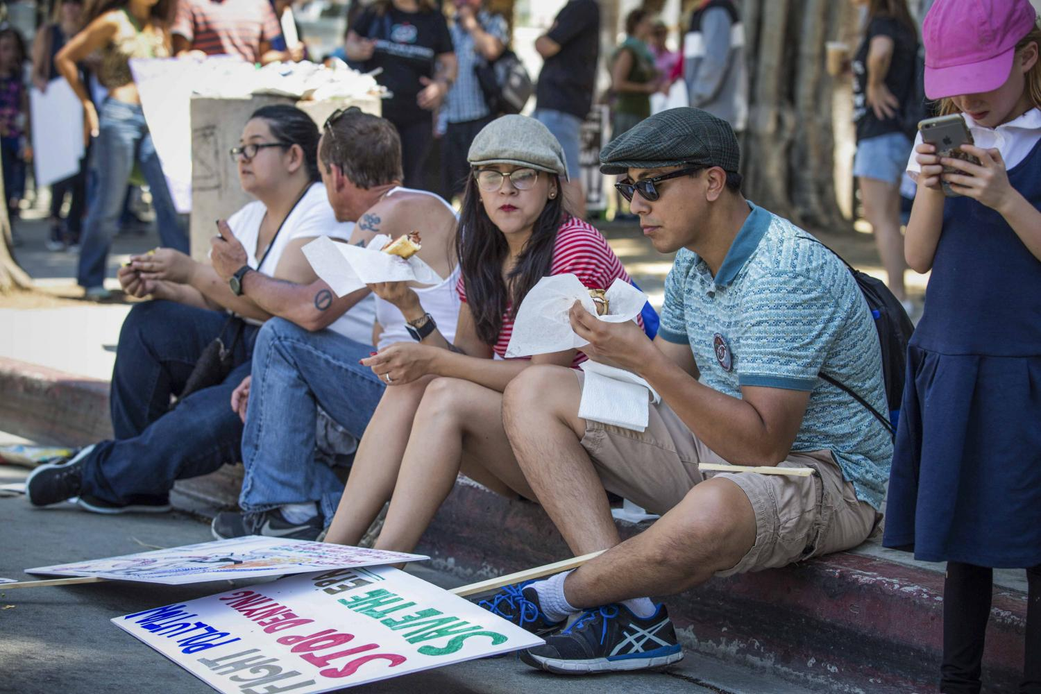 March for Science protesters take a break from the heat and eat in the shade after the majority of key speakers had wrapped up their speeches in front of Los Angles City Hall in downtown Los Angles California, on Saturday, April 22 2017. Matthew Martin.