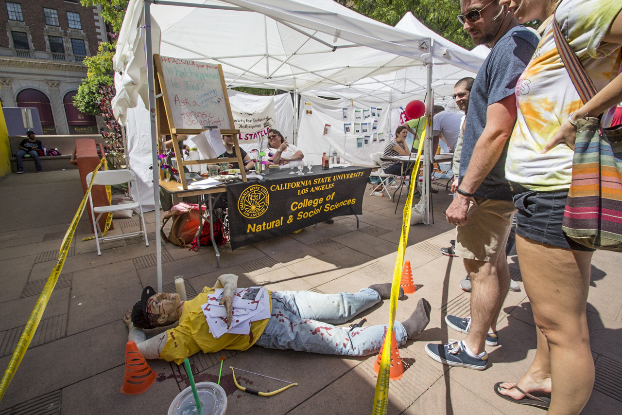 """""""Ask a forensic scientist!"""" The March for Science in Downtown Los Angeles had several booths, like this one for CSUNs College of Natural & Social Sciences. They set up a crime scene to make it more interesting. April 22, 2017. (Jazz Shademan)"""