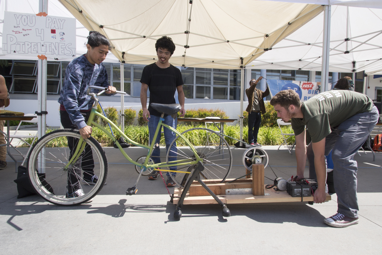 Bike Club sets up their charging bicycle for Earth Week at Santa Monica College on April 18, 2017. Justin Okobu Bike Club member (center) watches as Henry Haprov, who built the stationary bike that charges as you pedal, move it into the shade. Students can ride the bike and connect their chargers for phones, laptops, tablets etc. (Jazz Shademan)