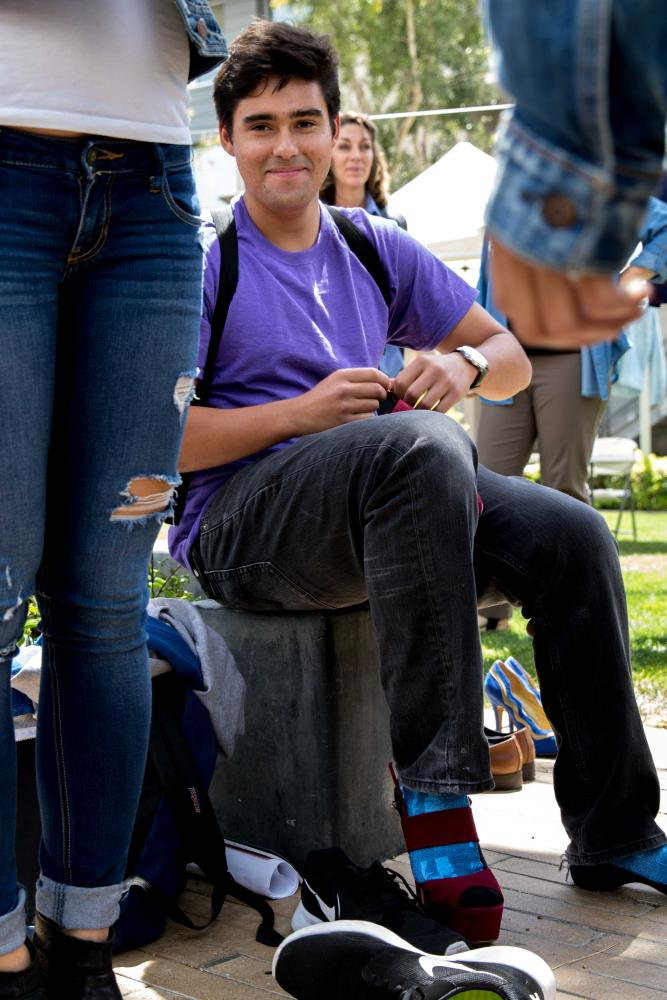 """Santa Monica College student Juan Parra straps on his high heels to attempt to """"Walk a mile in her shoes"""". This activity is designed for males to see one of the many difficulties women face on a day to day basis. This was part of Santa Monica Colleges Consent Week which takes place at Santa Monica College in Santa Monica California on April 26, 2017. Zane Meyer-Thornton."""