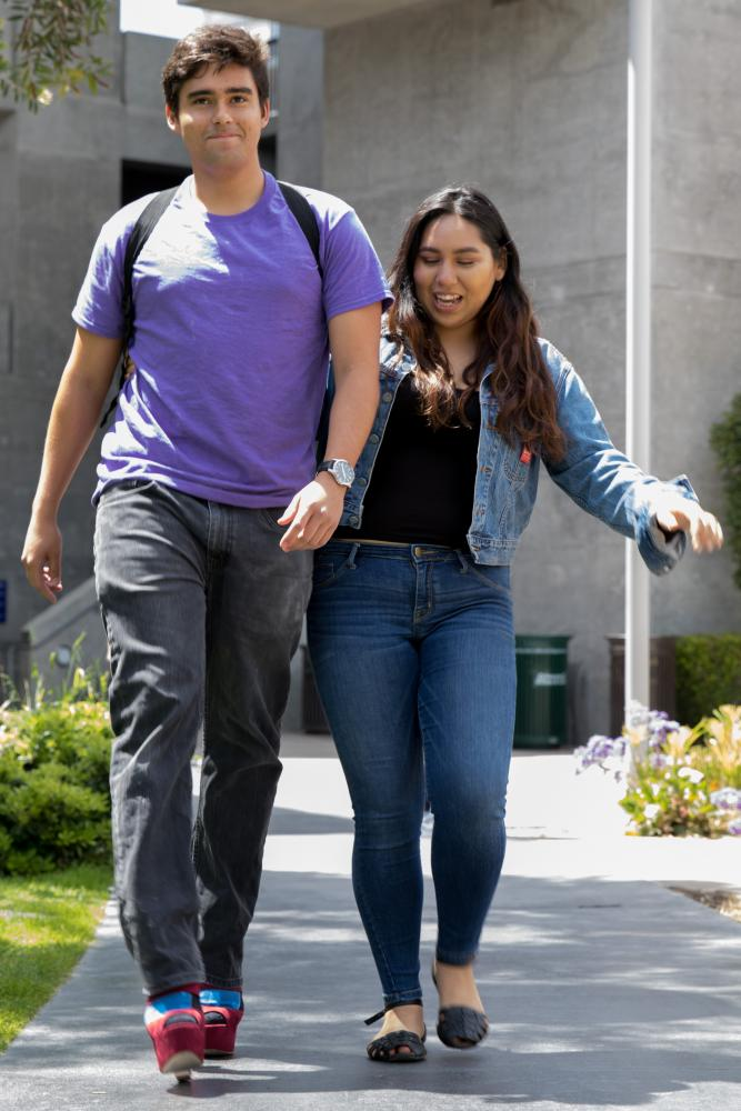 """Santa Monica College Student Juan Parra (left) is assisted by Isabel Castillo (right) as he attempts to walk in high heels as he attempts to """"Walk a mile in her shoes"""" to show support for victims of sexual misconduct as part of Santa Monica Colleges Consent Week which takes place at Santa Monica College, in Santa Monica California on April 26, 2017. Zane Meyer-Thornton."""