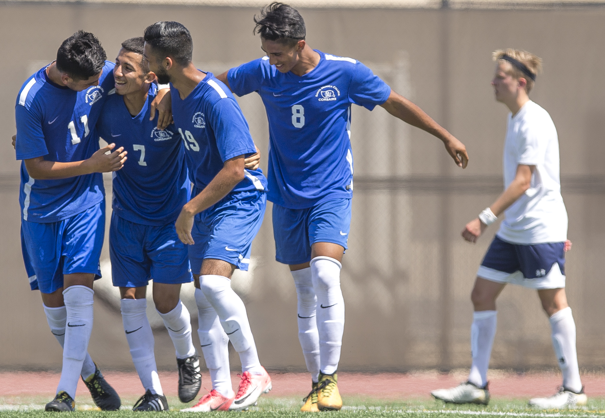 Kevin Martinez (blue,left) (7) of the Santa Monica College Corsairs mens soccer team celebrates a goal against the El Camino College Warriors with his teamates, Friday, September 1st, 2017, at the Santa Monica College Main Campus field in Santa Monica, California. The Corsairs beat The Warriors 5-1. (Daniel Bowyer/Corsair Staff)