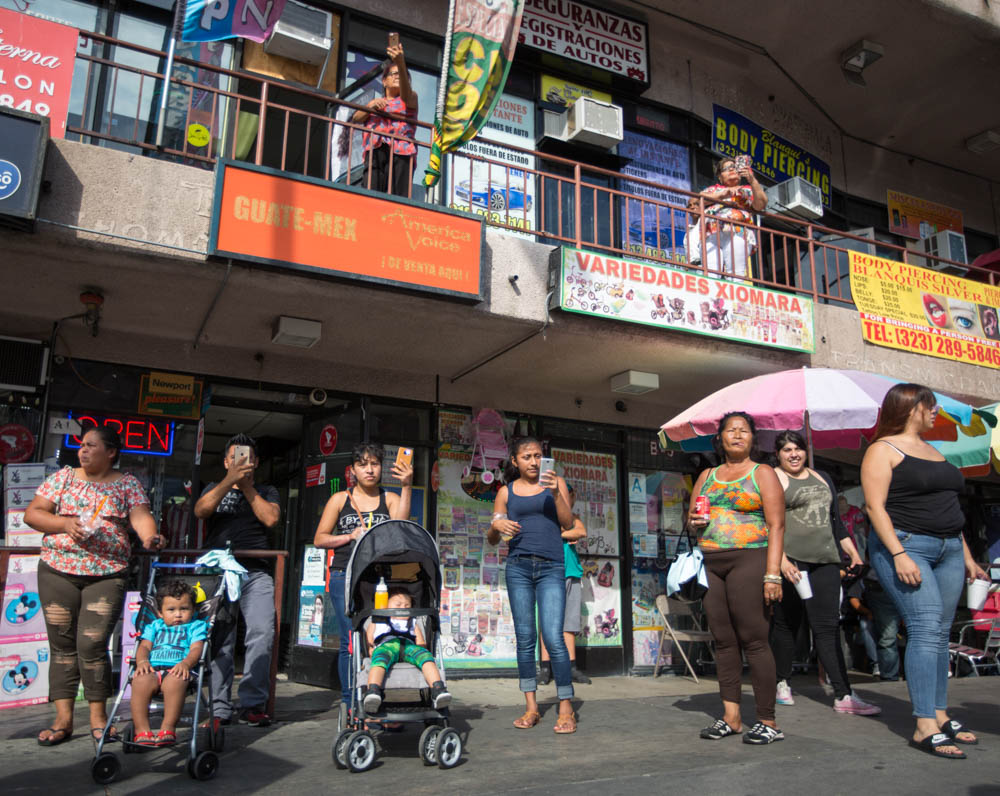 Shoppers along 6th street near MacArthur Park watch the pro-DACA supporters begin their march to Olvera Street on September 10, 2017 in Los Angeles, California. (Jose Lopez)