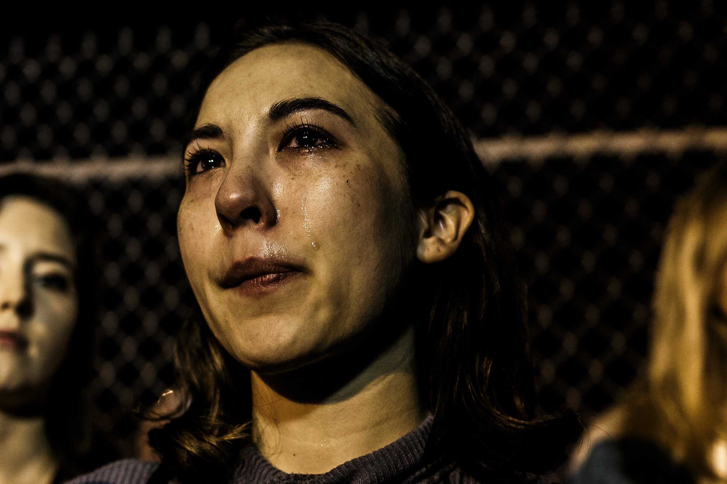 Christina Sewell, a senior campaigner for PETA, cries silently as the trucks containing pigs destined for slaughter drive slowly in through the gates of Farmer John, a slaughterhouse in Vernon, CA on March 13 2017.