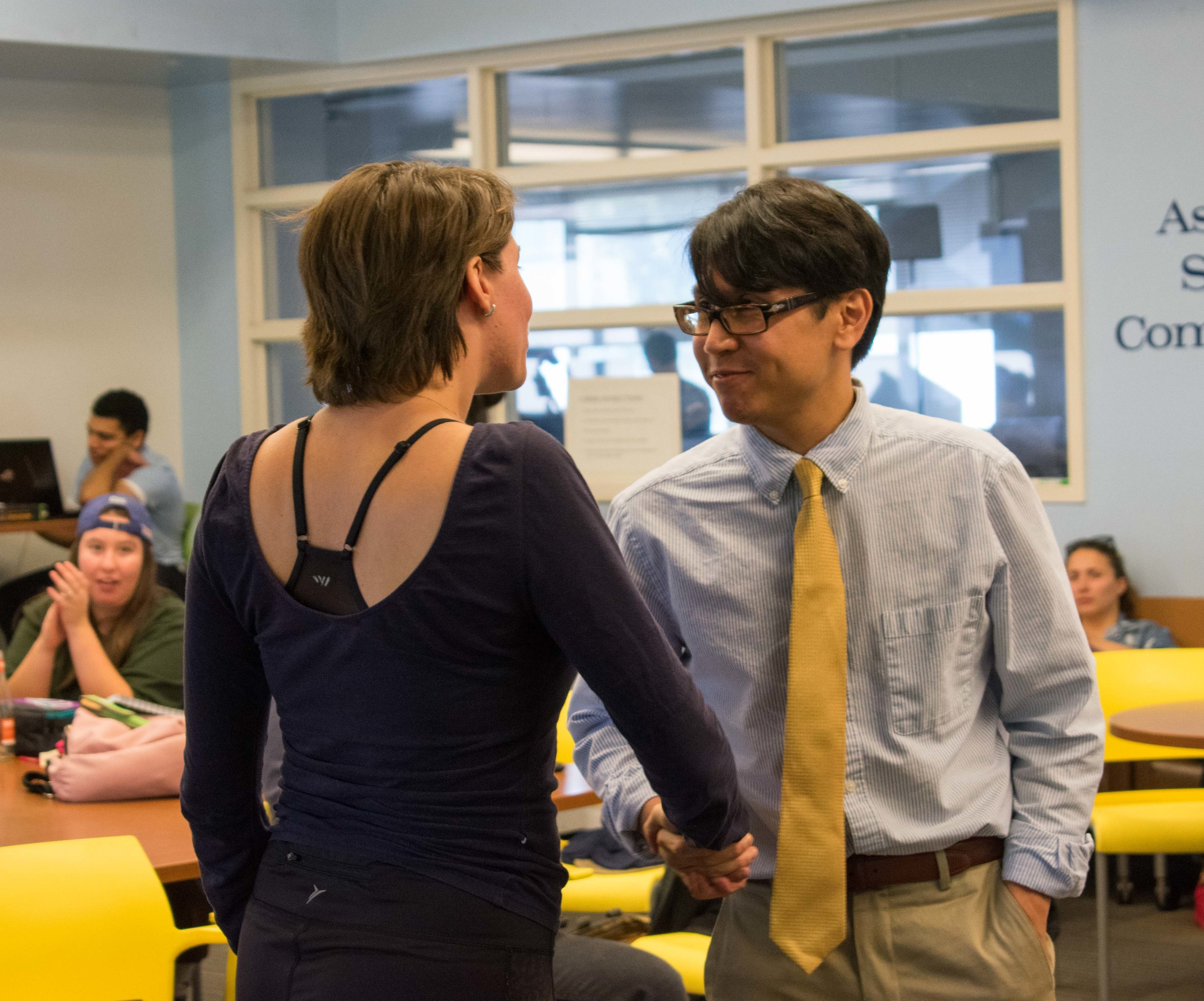 Ana Laura Paiva shakes the hand of Arthur Sanchez moments after Paiva is voted to be the director of student assistance at Santa Monica College in Santa Monica, California. (Photo by Ethan Lauren)