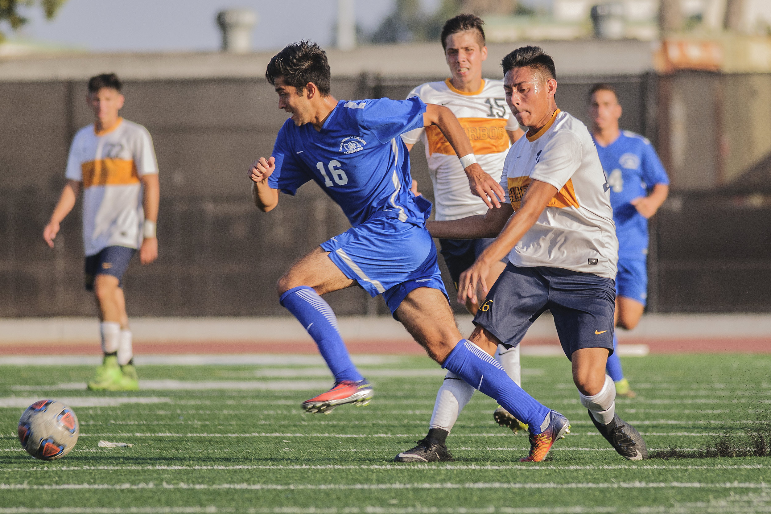 Left Carlos Rincon from the Santa Monica College mens soccer team dribbles the soccer ball around Michael Garcia from the Los Angeles Harbor College mens soccer team in white at corsair field located on the campus of smc on Tuesday September 19th 2017 as SMC hosted Harbor College in a non league soccer match and won 4-1 to remain undefeated this season with a record of 5 wins and 1 tie. Watching on behind the two of them is Garcia's teammate Roberto Gerardo
