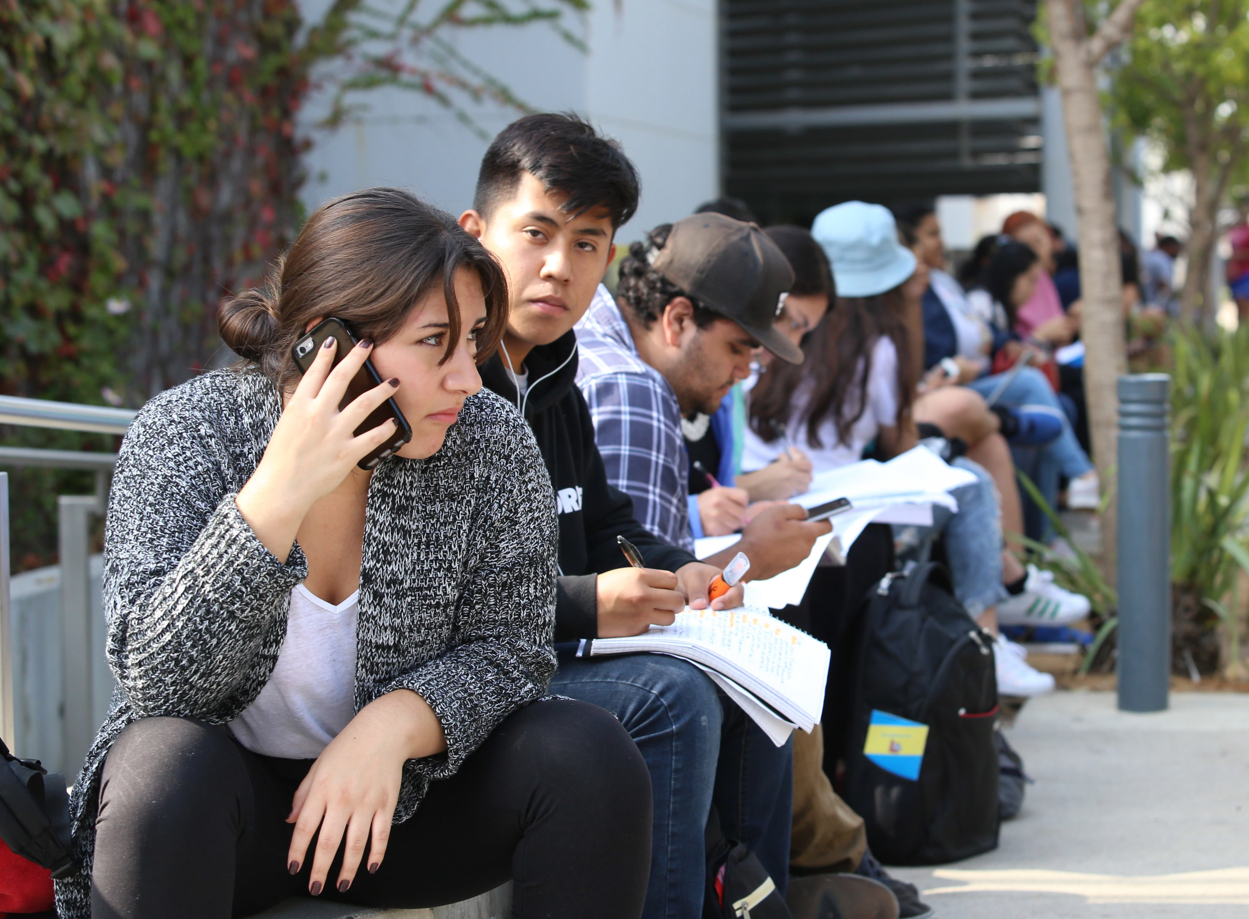 Students wait outside of Santa Monica College's Main Campus Library doing school work after being evacuated for the Great California Shakedown drill in Santa Monica, Calif on Thursday, October 19th 2017. (Photo by: Thane Fernandes)