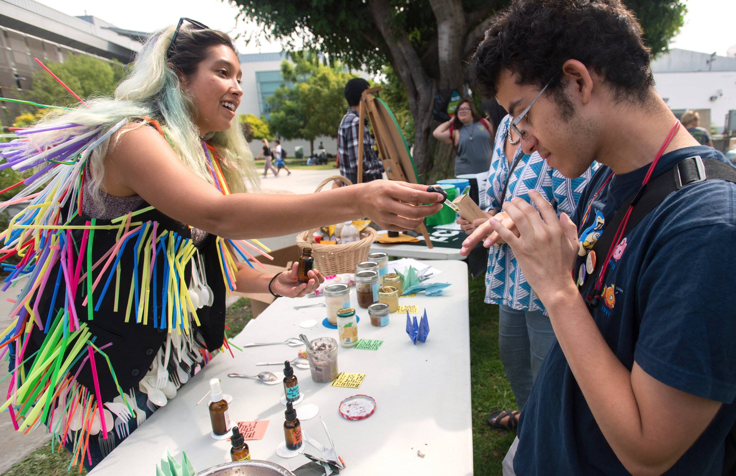 Carla Claure, 28, (L) Vice President of Eco Action club demonstrates oil samples for men to Anthony Carrillo, 20, (R) a Psychology major during Sustainability Week at Santa Monica College, in Santa Monica, California on October 17, 2017. (Josue Martinez)