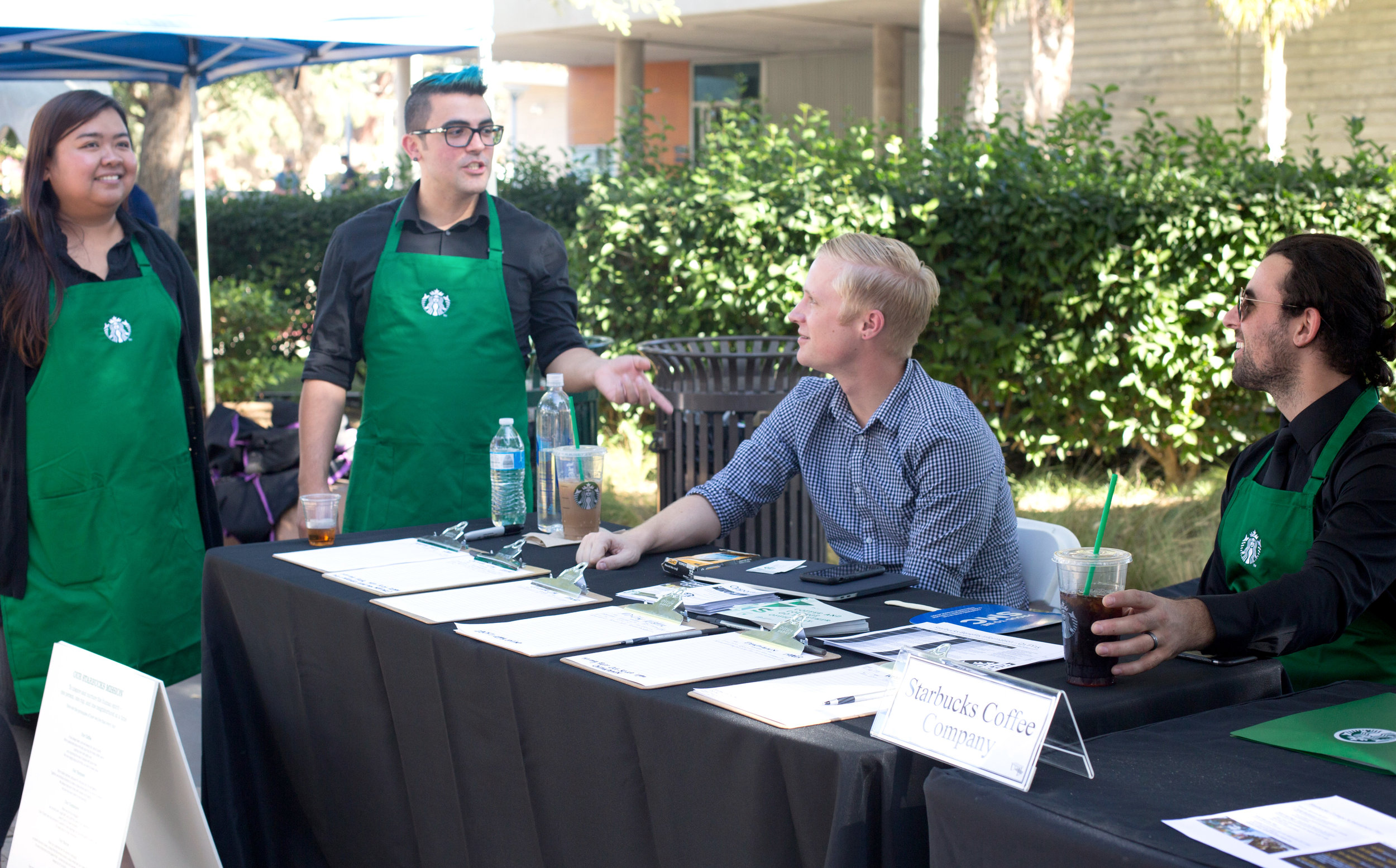 (L to R) Starbucks Store Managers Carla Henriquez and Vincent Perez at the Starbucks employment booth with District Manager August Anderson and Store Manager Jarrod Jacobus scouting for friendly faces in the student population at the Job Fair in Santa Monica College in Santa Monica, Calif., October 24, 2017. (Photo By: Ripsime Avetisyan/Corsair Staff)