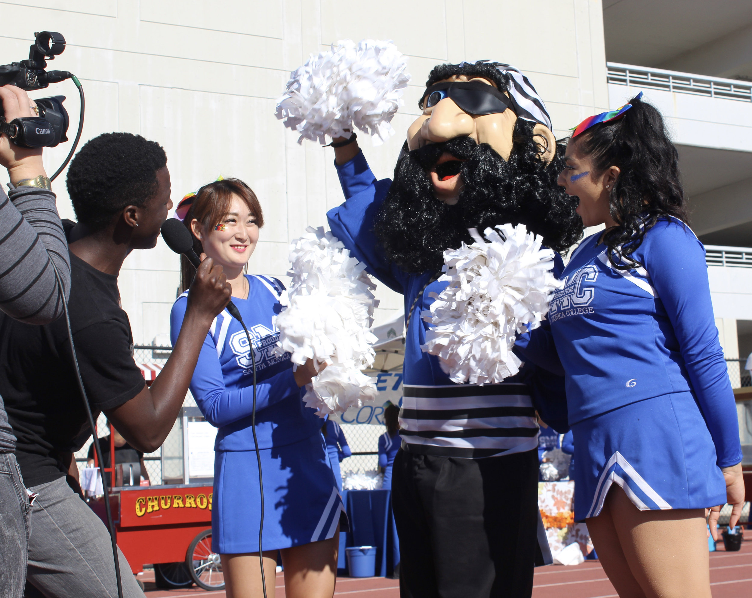 Santa Monica College student and Urban Mediamakers West Club member Sambie Mwafulirwa interviewing Cheer Club members and the Corsiar mascot during the Homecoming Tailgate Party Saturday morning on November 4, 2017 on the athletic field at SMC. UMW club members filmed the Tailgate Party festivities. (Photo by Jessica Uhler)
