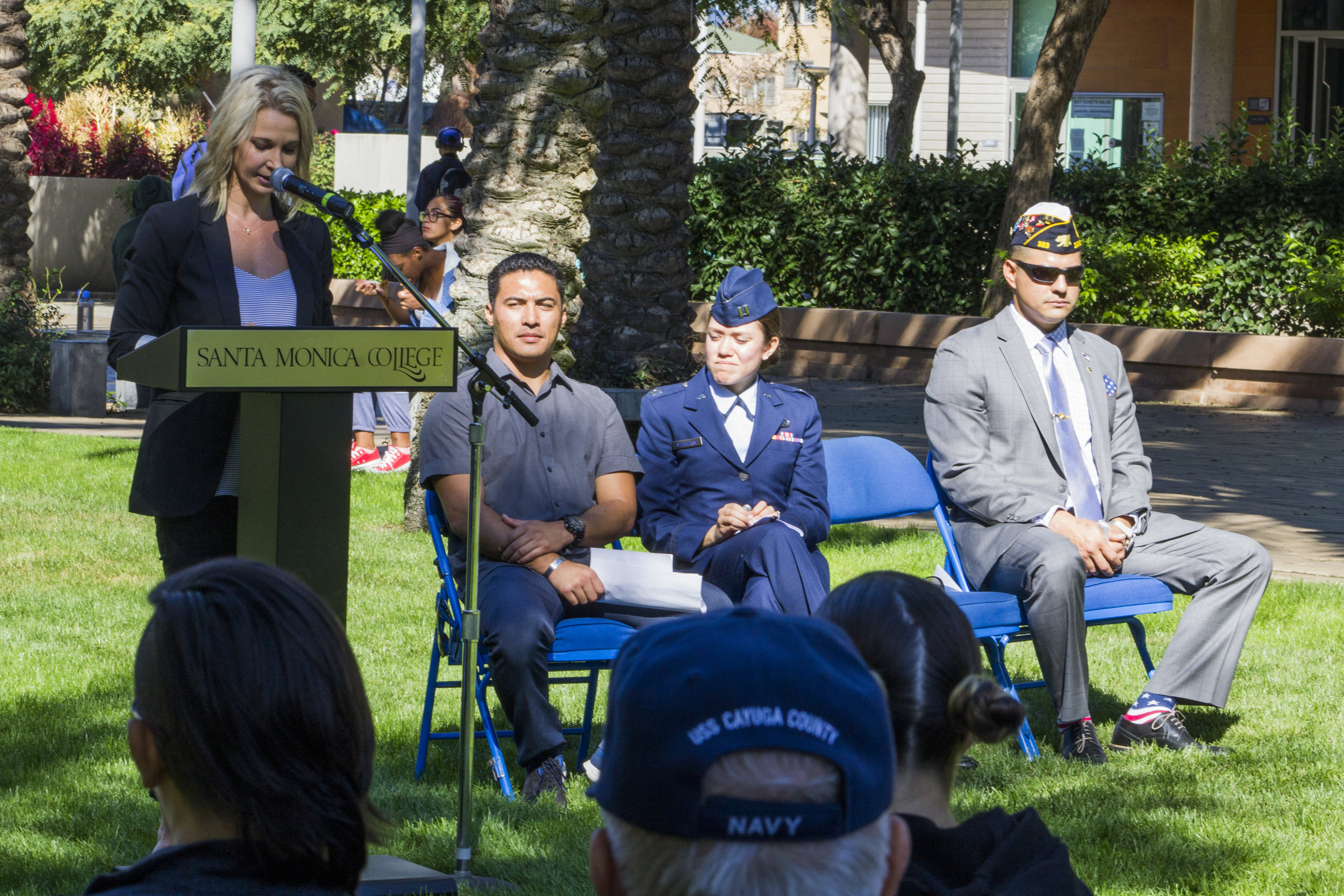 """Standing speaker, US Army Veteran Jennifer Campbell, next to (L. to R.) the President of the Student Veterans Association of Santa Monica, US Air Force Veteran Beau Espeso, US Air Force Captain Brittany Campbell and the Veteran Student Speaker from the US Marine Corps Noe Aguirre. During the Veterans Day ceremony, """"Honoring Those Who Served"""", at the Santa Monica College Main Campus, by the quad, Santa Monica, Calif. On Thursday Nov.9, 2017. Photo by Emeline Moquillon."""