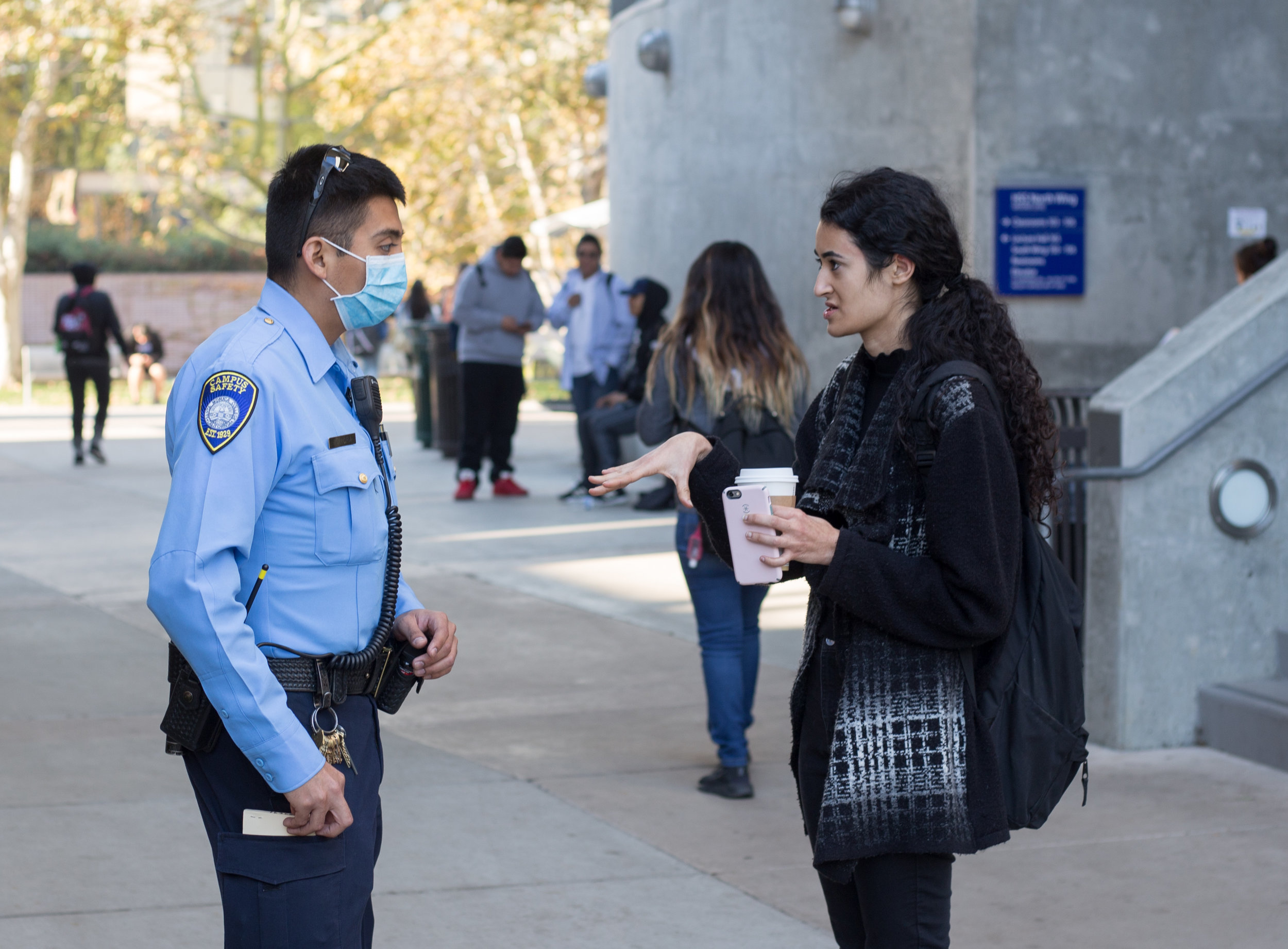 """A Santa Monica Student (right) asks Campus Safety Officer Zamora (left) about why all classes were canceled after an email was sent out at 8:49 am by SMC informing students that classes are canceled due to the close proximity to the Skirball fire on Wednesday, December 6th 2017 in Santa Monica, Calif. The email stated that the """"fire is affecting the air quality and the road conditions in and around SMC area"""". (Photo by: Thane Fernandes)"""
