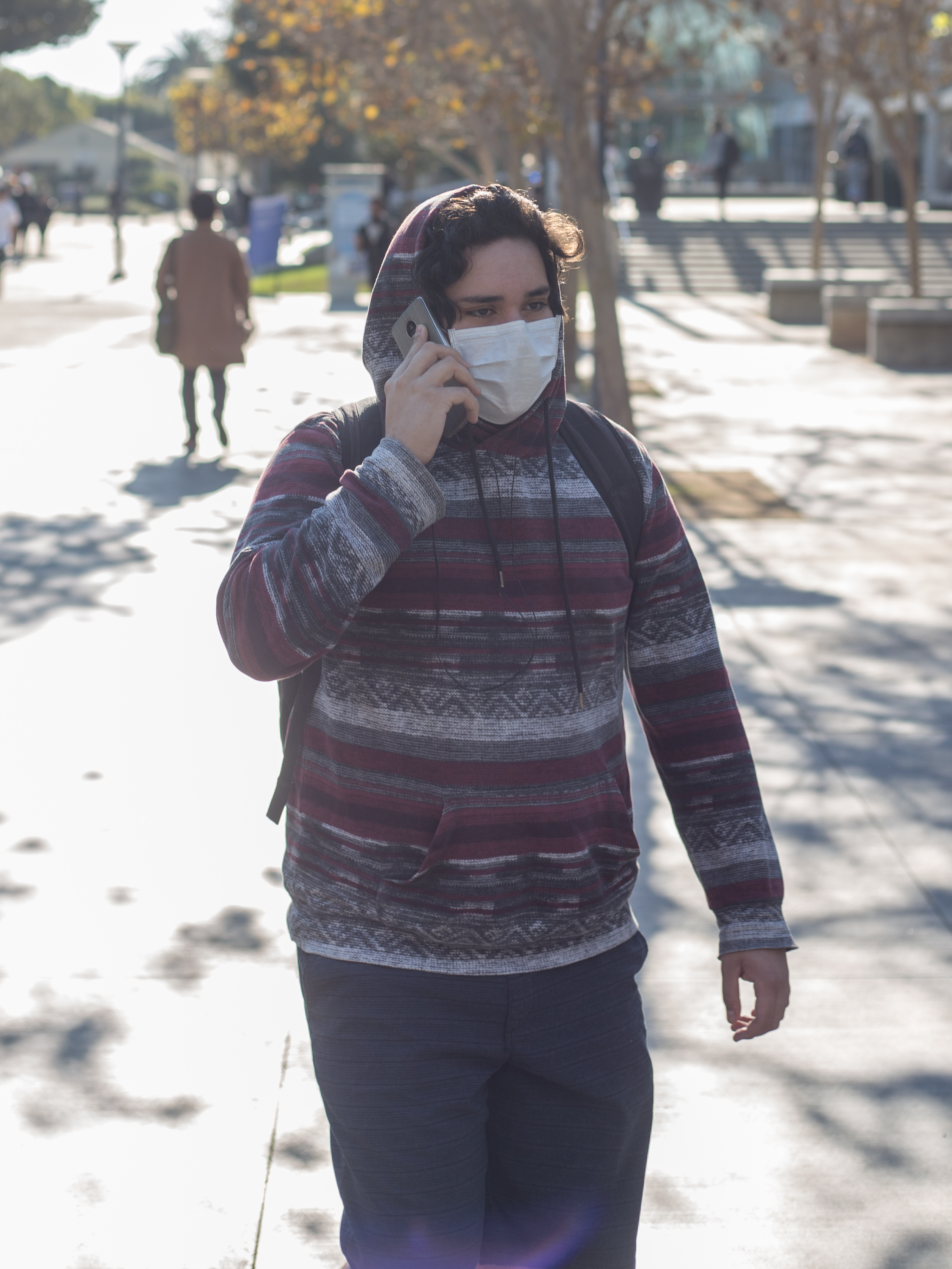 """SMC Student walks on campus with a mask over his mouth and nose due to the poor air quality as a result from the Skirball fire after an email was sent out at 8:49 am by SMC informing students that classes are canceled due to the close proximity to the Skirball fire on Wednesday, December 6th 2017 in Santa Monica, Calif. The email stated that the """"fire is affecting the air quality and the road conditions in and around SMC area"""". (Photo by: Thane Fernandes)"""